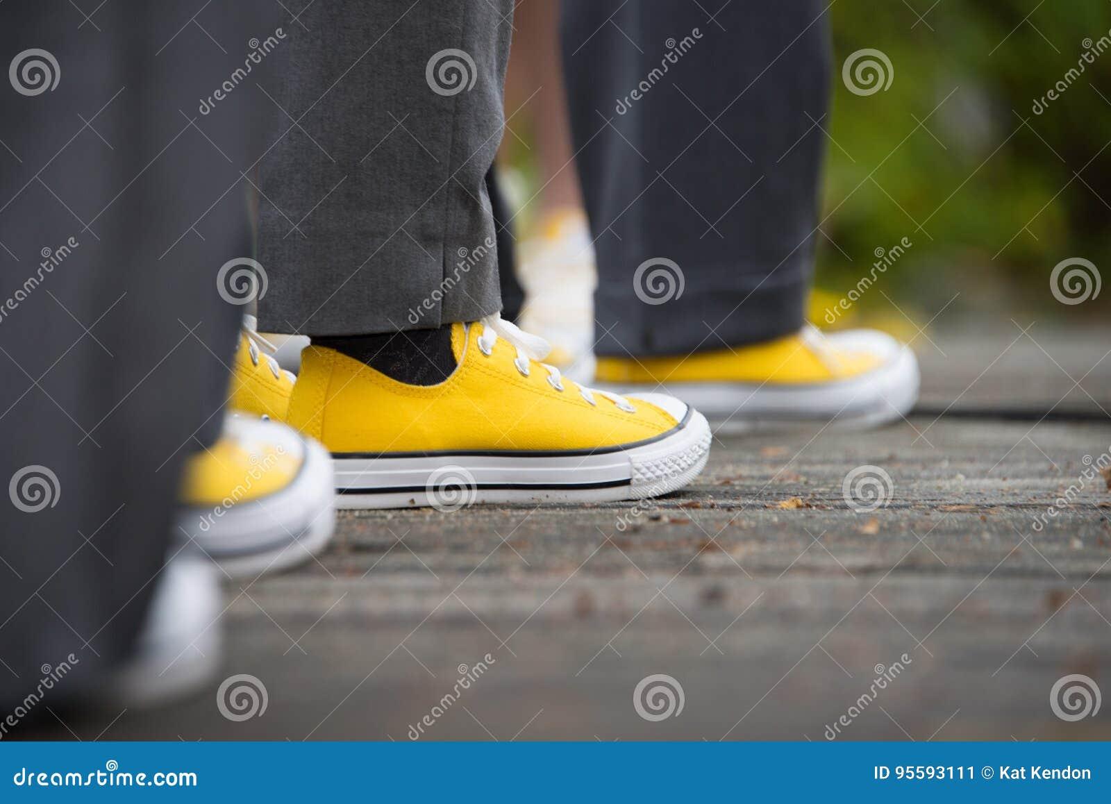 Gelbe gegenteilige Turnschuhe mit grauen Durchhängen an einer Hochzeit