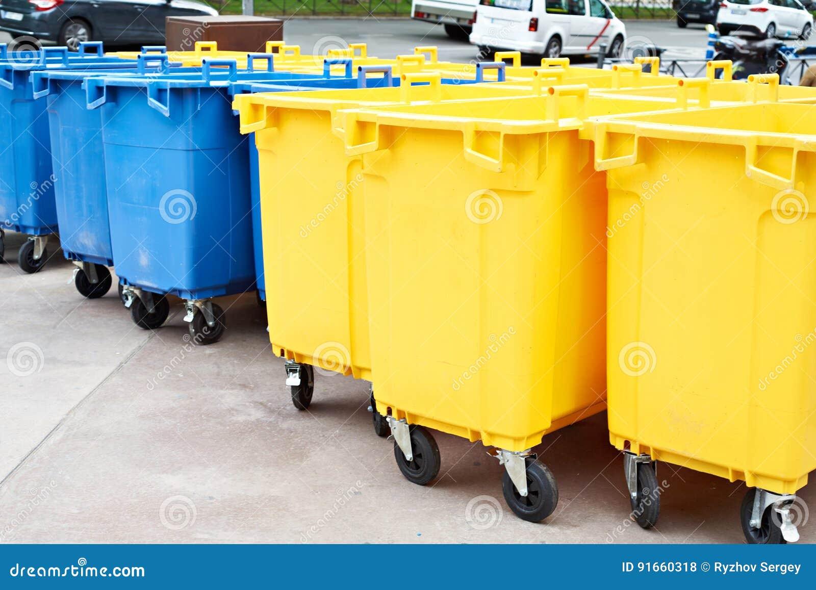 Gelbe Und Blaue Plastikmulleimer Auf Stadtstrasse Stockfoto Bild