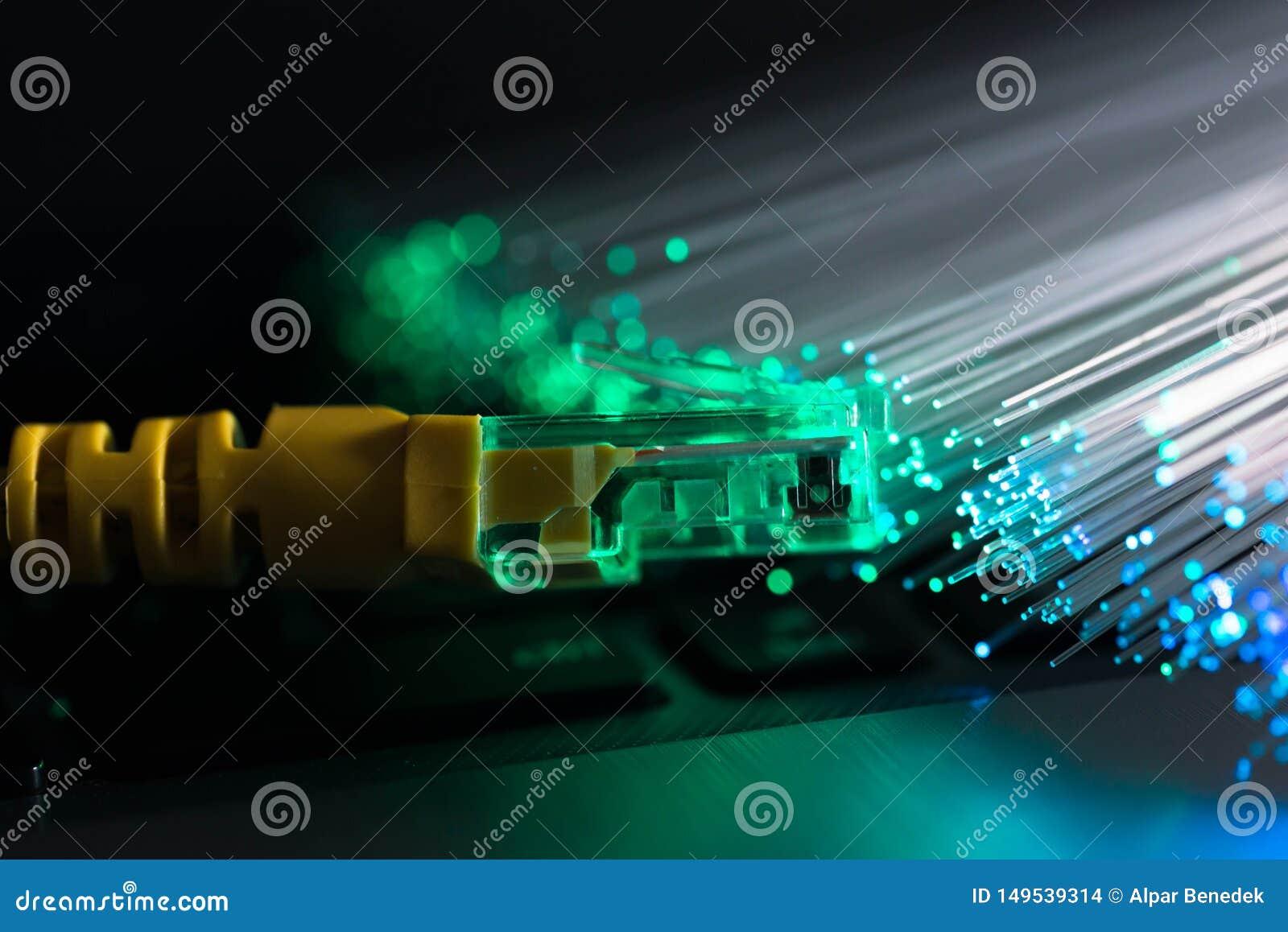 Gelber Internet-Schalter, gl?hende Glasfasern auf Laptop-Computer