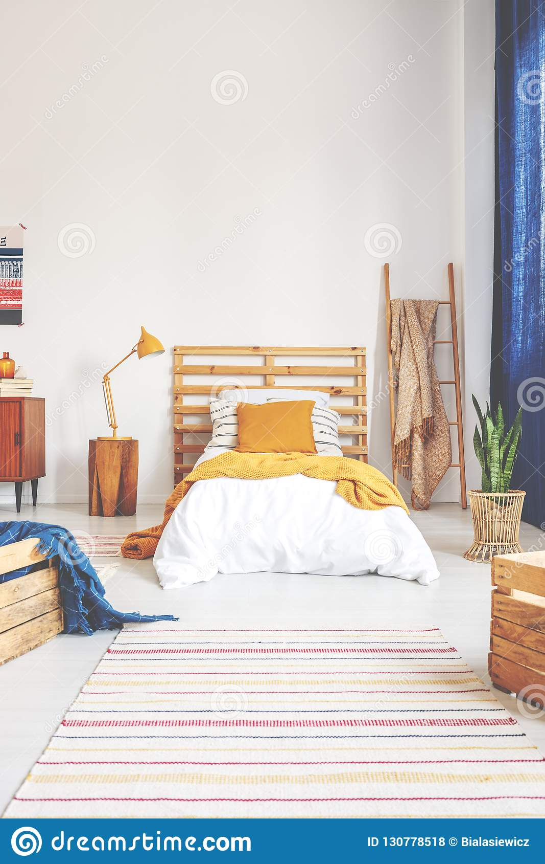 Gelbes Kissen und Decke auf bequemem weißem hölzernem Bett im Jugendlichschlafzimmer mit abgestreiftem Teppich auf dem Boden