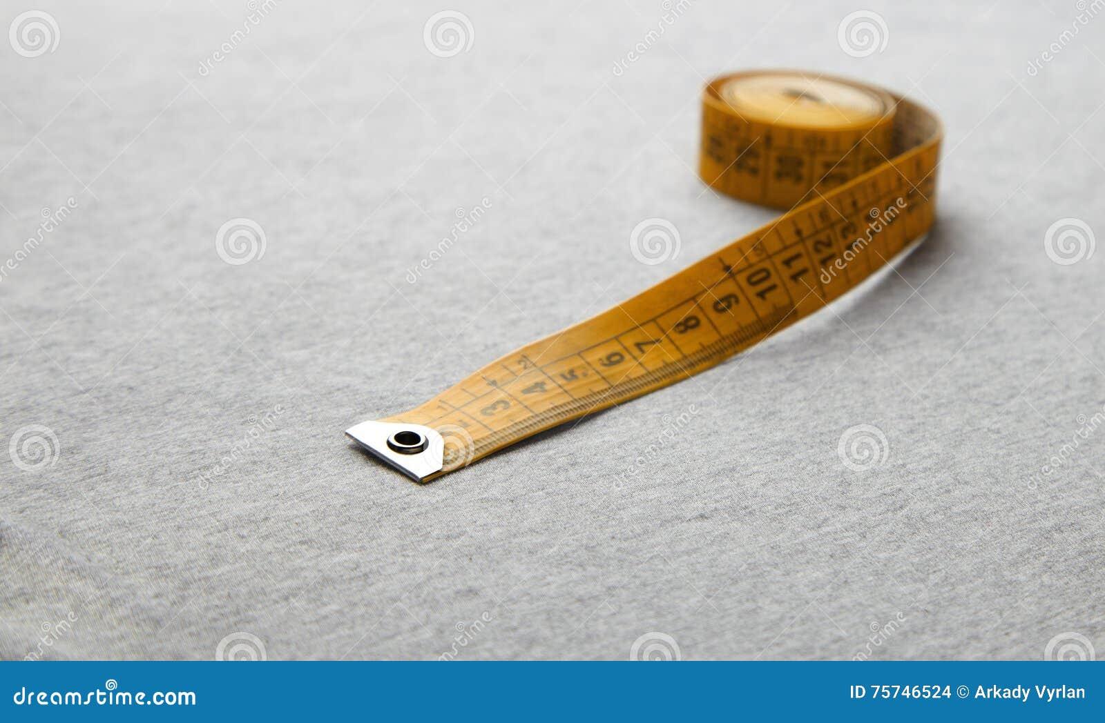 Gelbes messendes Band auf grauem Gewebe