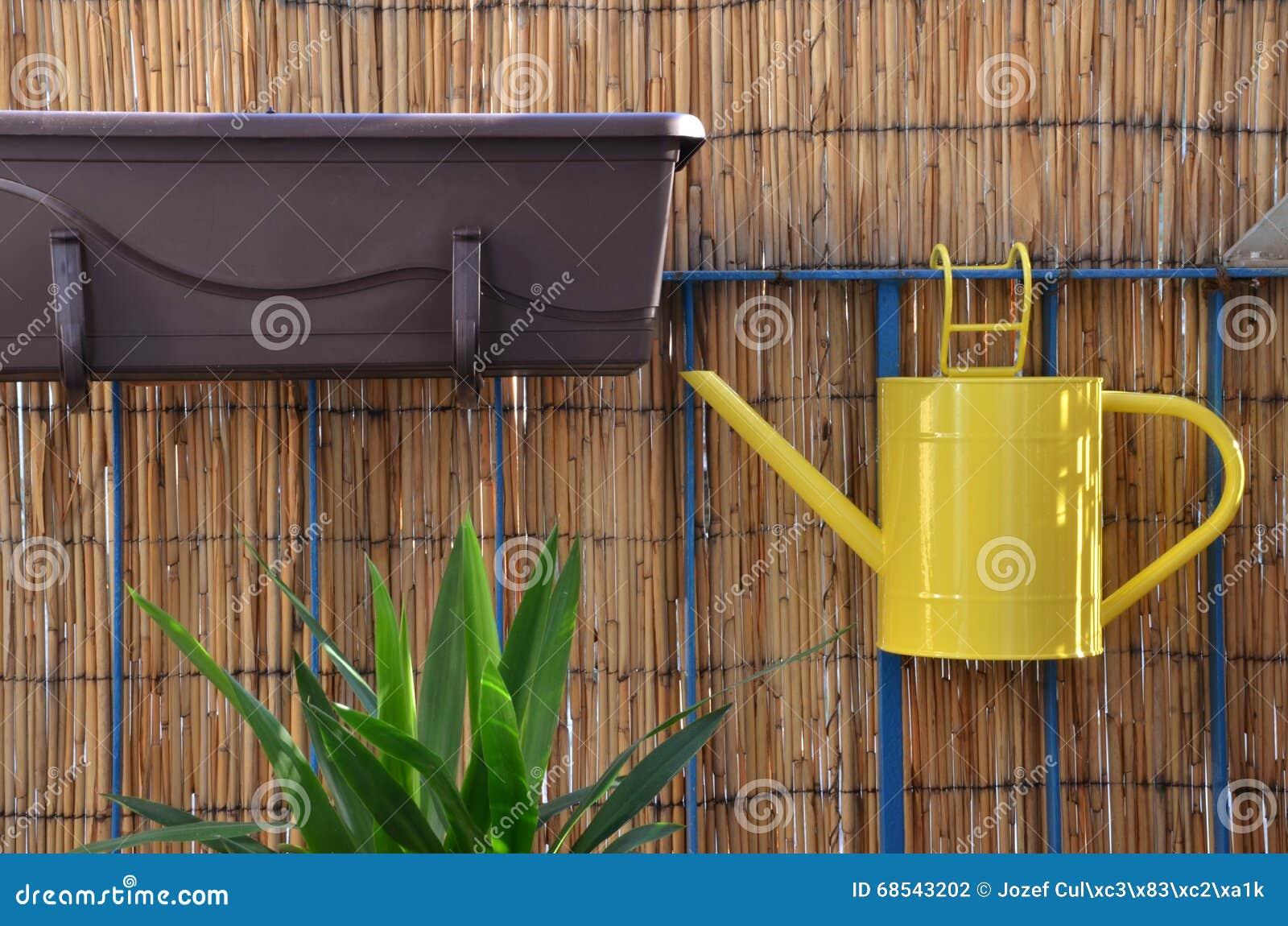 gelbes metallgießkannefall auf balkongeländer, bambuszaun im
