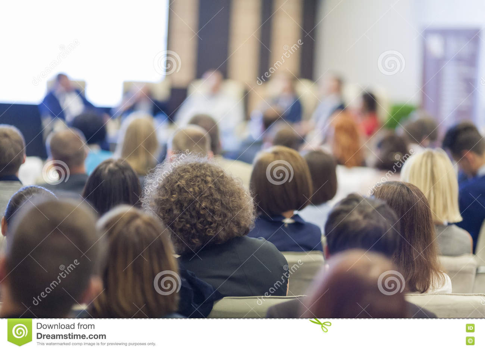 Geld mit Rechner Leute bei der Konferenz hörend auf die Wirts-Sprecher, die in Front On Stage Before The-Publikum sitzen