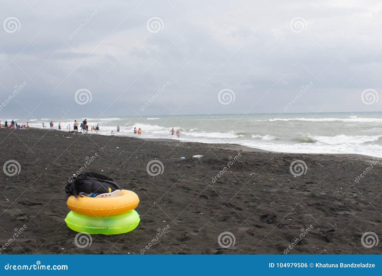 Gele en groene Drijvende Ring op strand, bewolking, wolken, golven