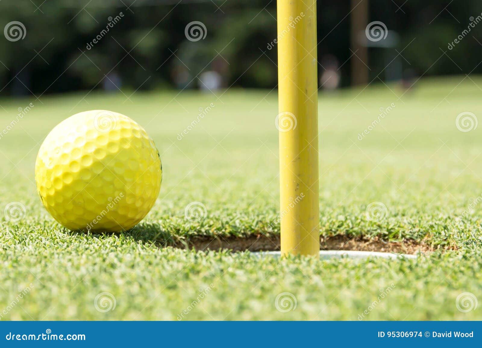 Gele golfbal op rand van gat