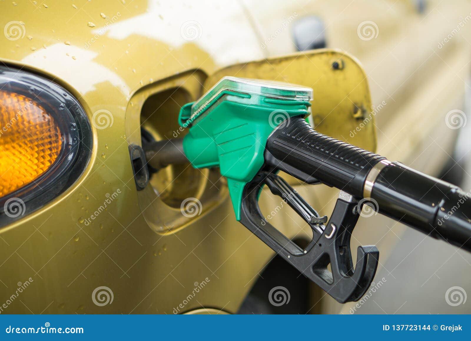 Gele, gouden auto bij een benzinestation die met brandstof worden gevuld