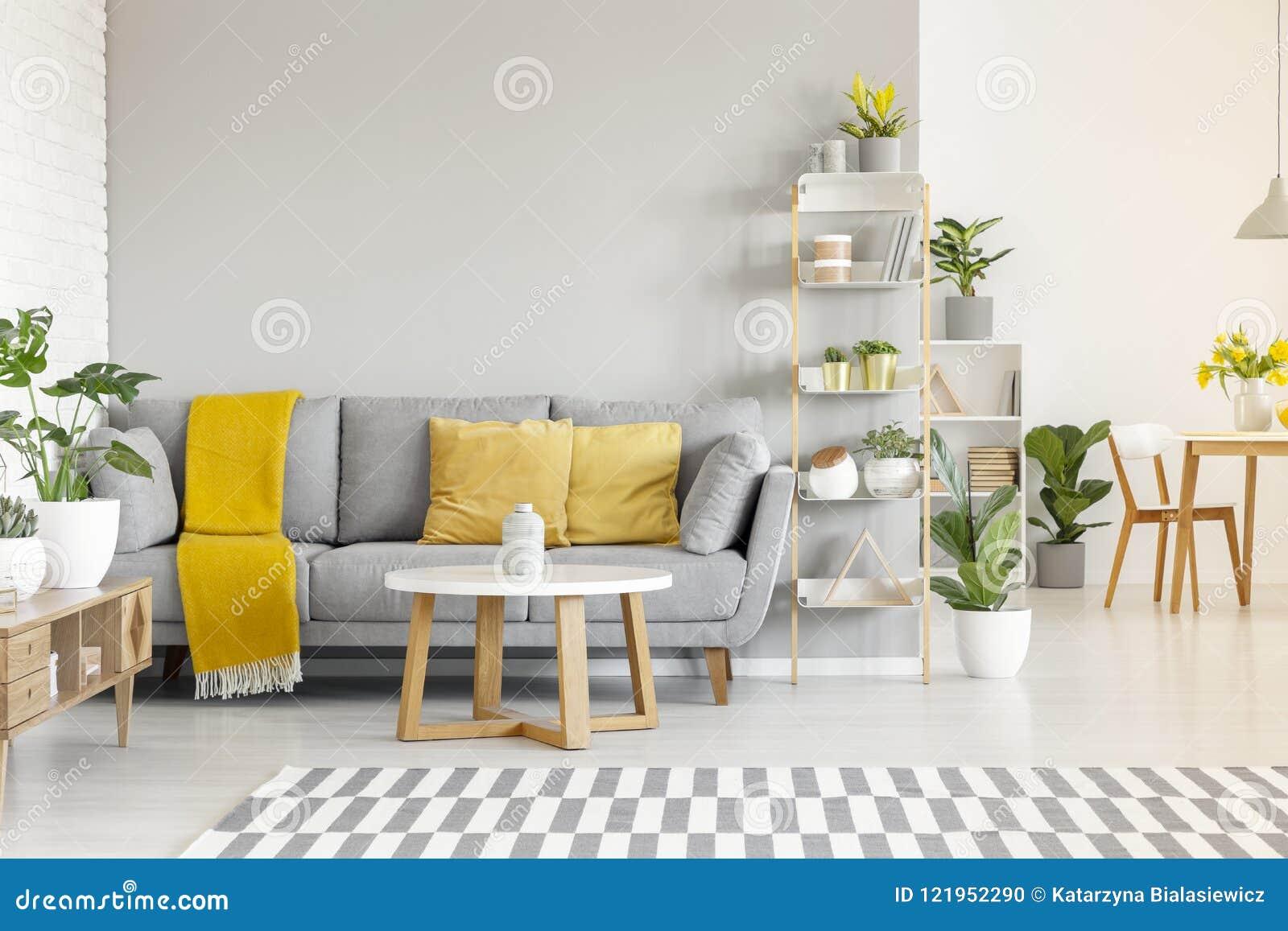 Gele hoofdkussens en deken op grijze bank in moderne woonkamer binnen