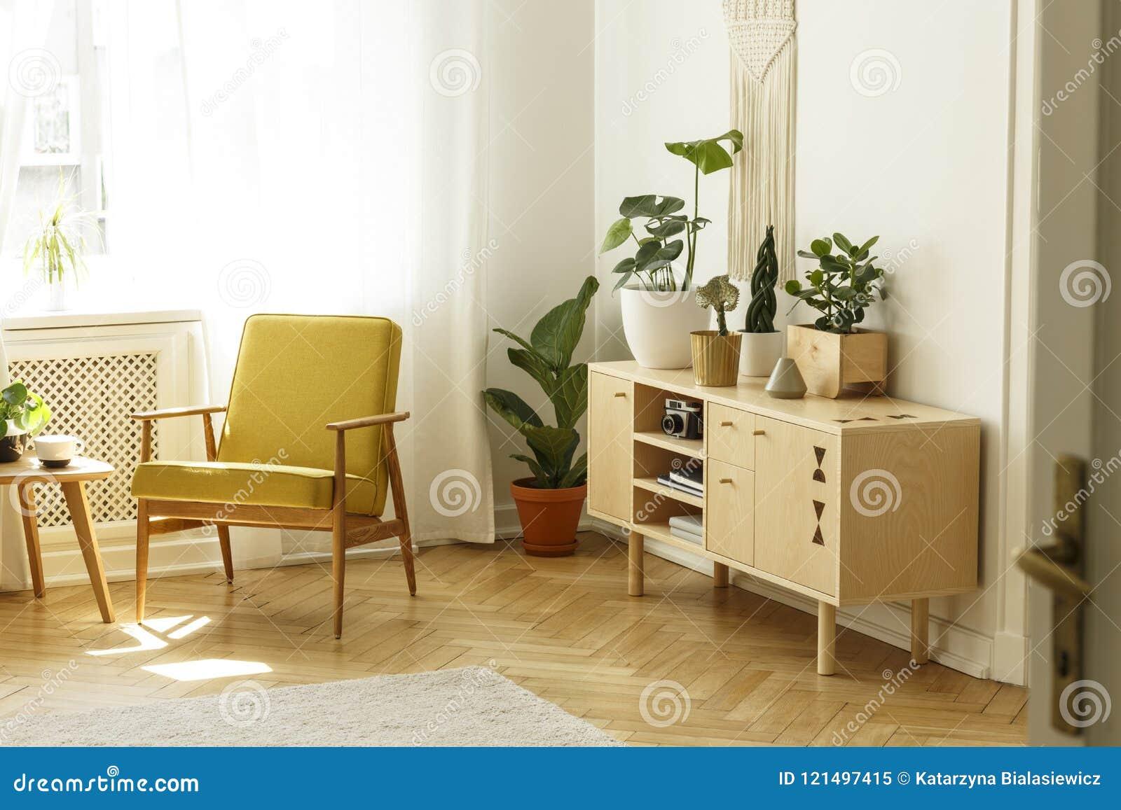 Gele houten leunstoel naast kabinet met installatie in heldere livi