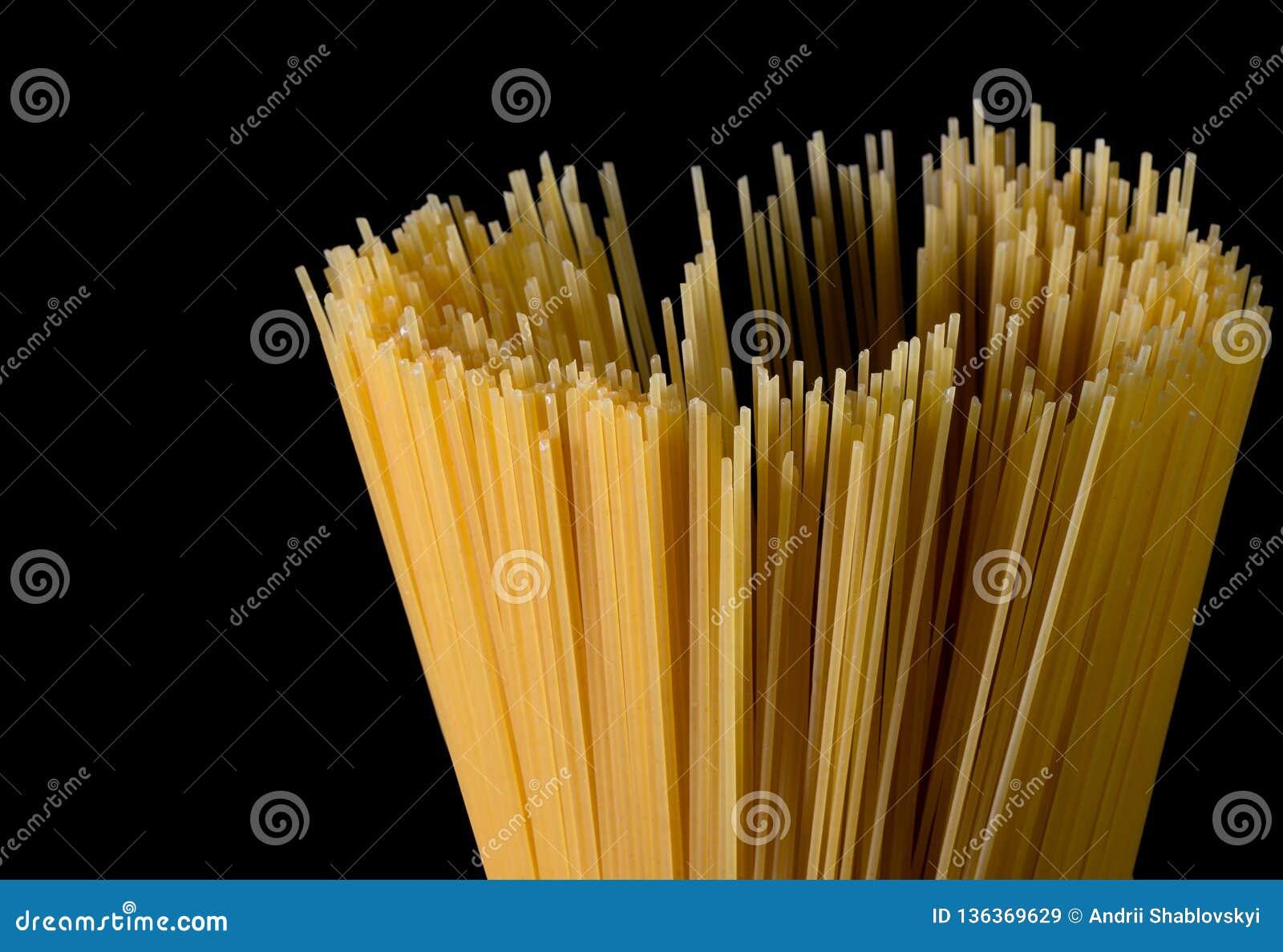 Gele lange spaghetti op zwarte achtergrond Dunne die deegwaren in rijen worden geschikt Gele Italiaanse deegwaren Lange spaghetti
