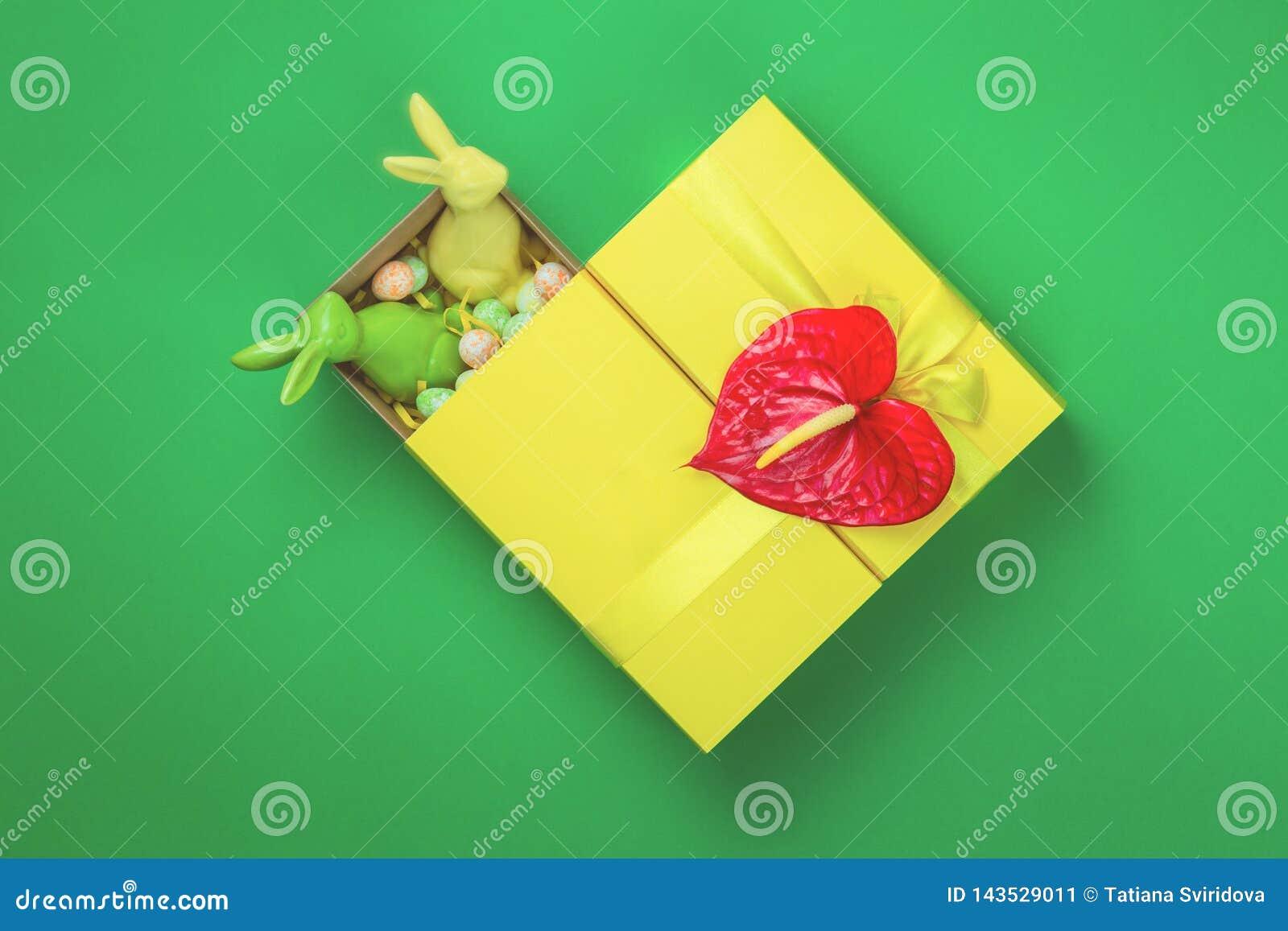Gele Pasen giftbox met twee konijntjes op groene achtergrond