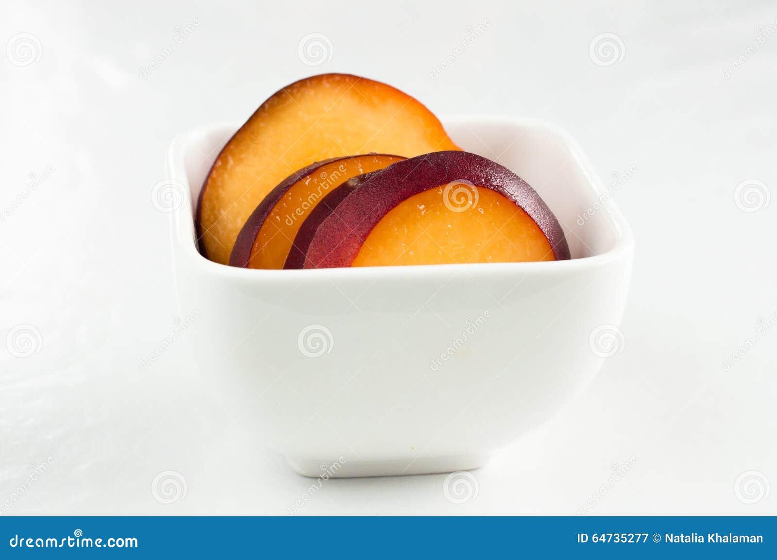 Gele perziken in witte vierkante kom