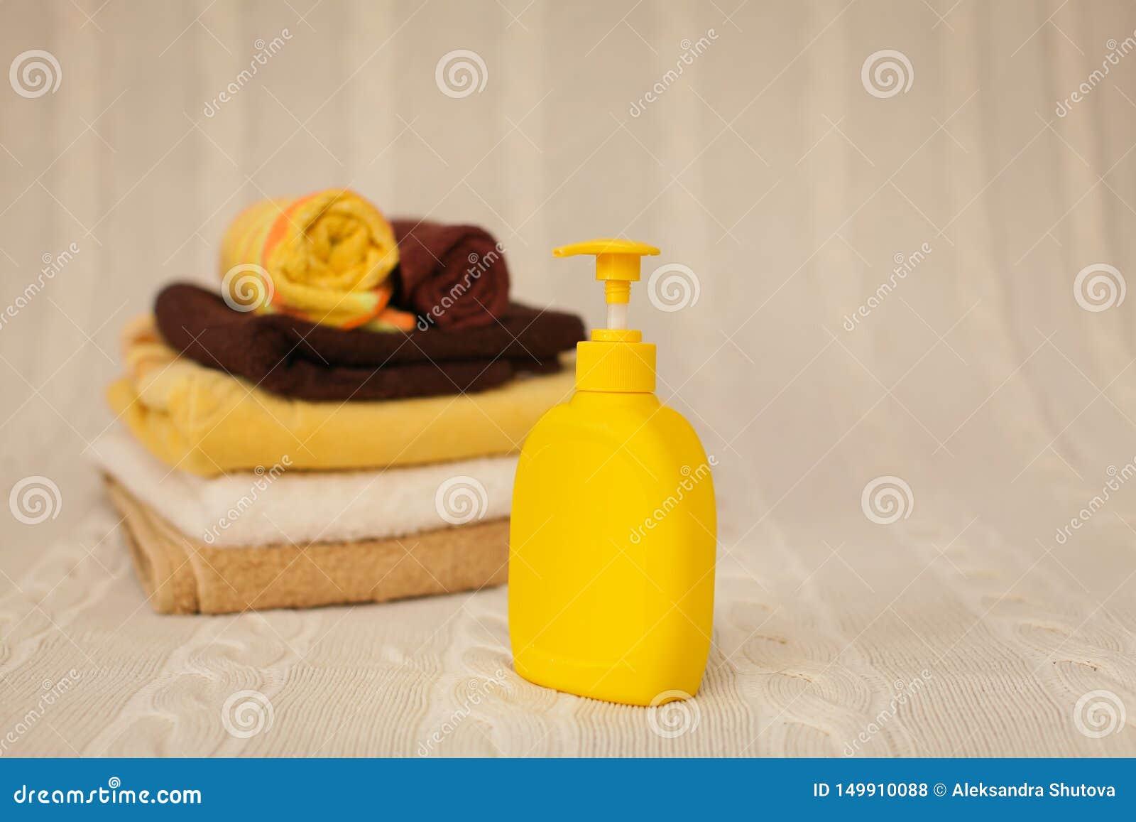 Gele plastic automaat met vloeibare zeep en een stapel bruine handdoeken op een beige deken in selectieve nadruk