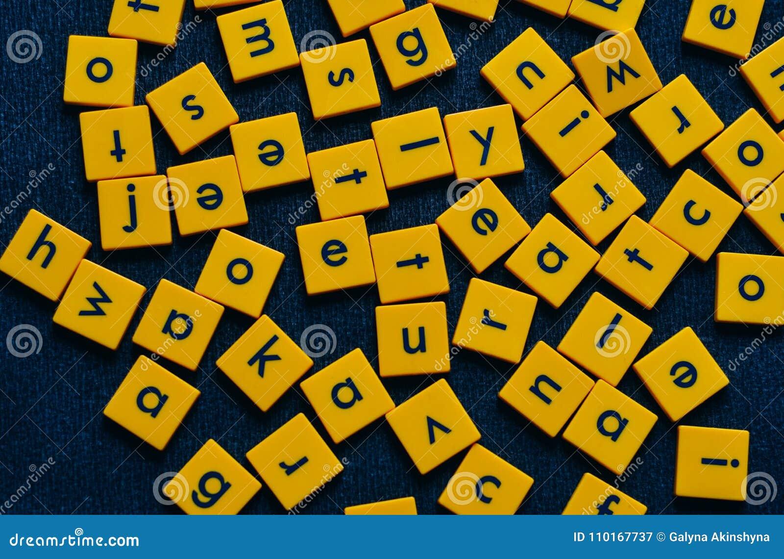 Gele tegels met zwarte brieven op zwarte achtergrond