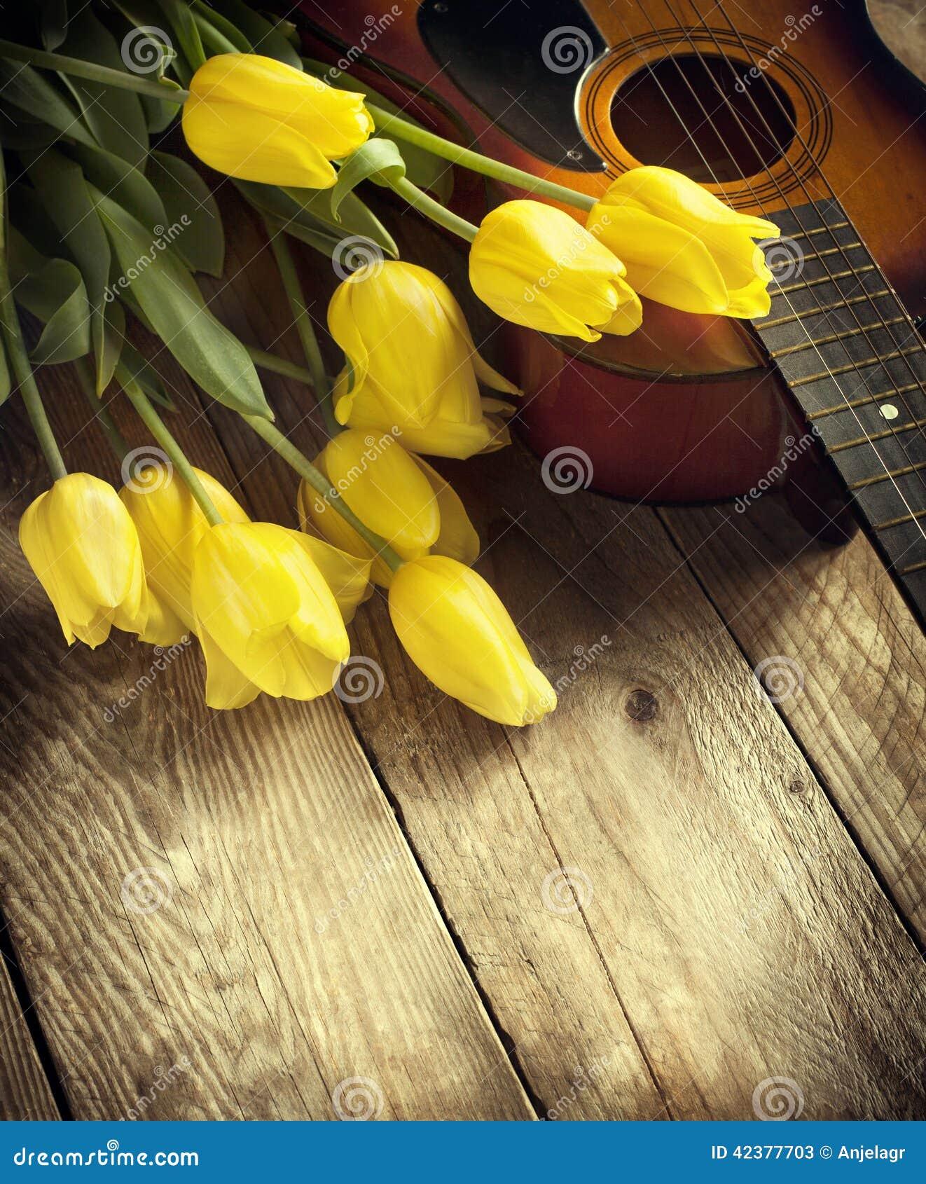 Gele tulpen en gitaar op oude houten oppervlakte Kleine diepte van fie