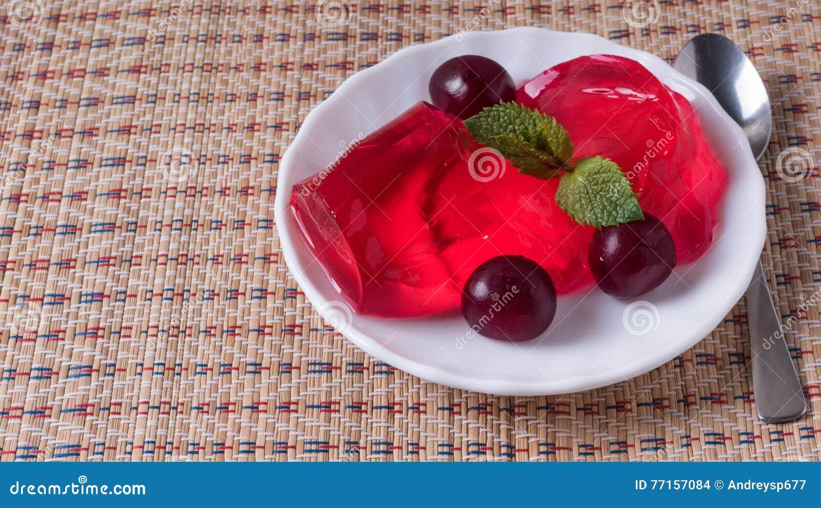 Gelez dans le plat blanc avec les cerises mûres