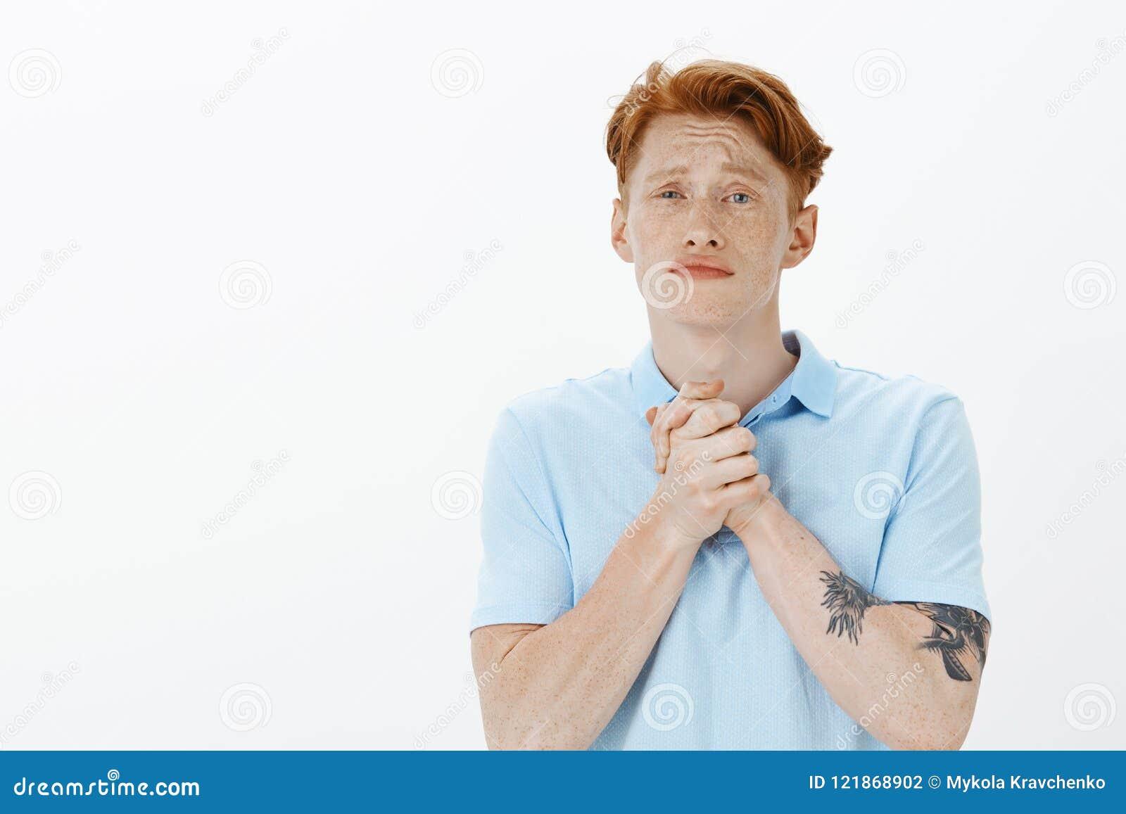Gelieve te doen me gunst Knappe gevoels slechte kerel met rode haar en sproeten, samen dichtklemmend handen over borst, het frons