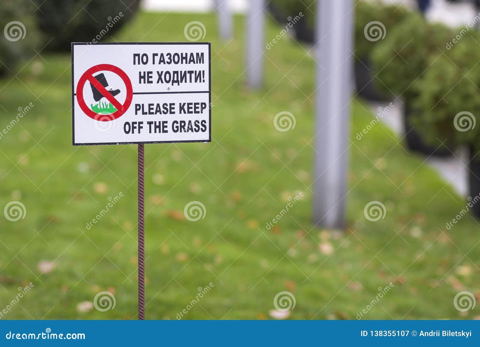 Gelieve te houden het grasteken op groene gazongras vage bokeh achtergrond op op een afstand zonnige de zomerdag Stadslevensstijl