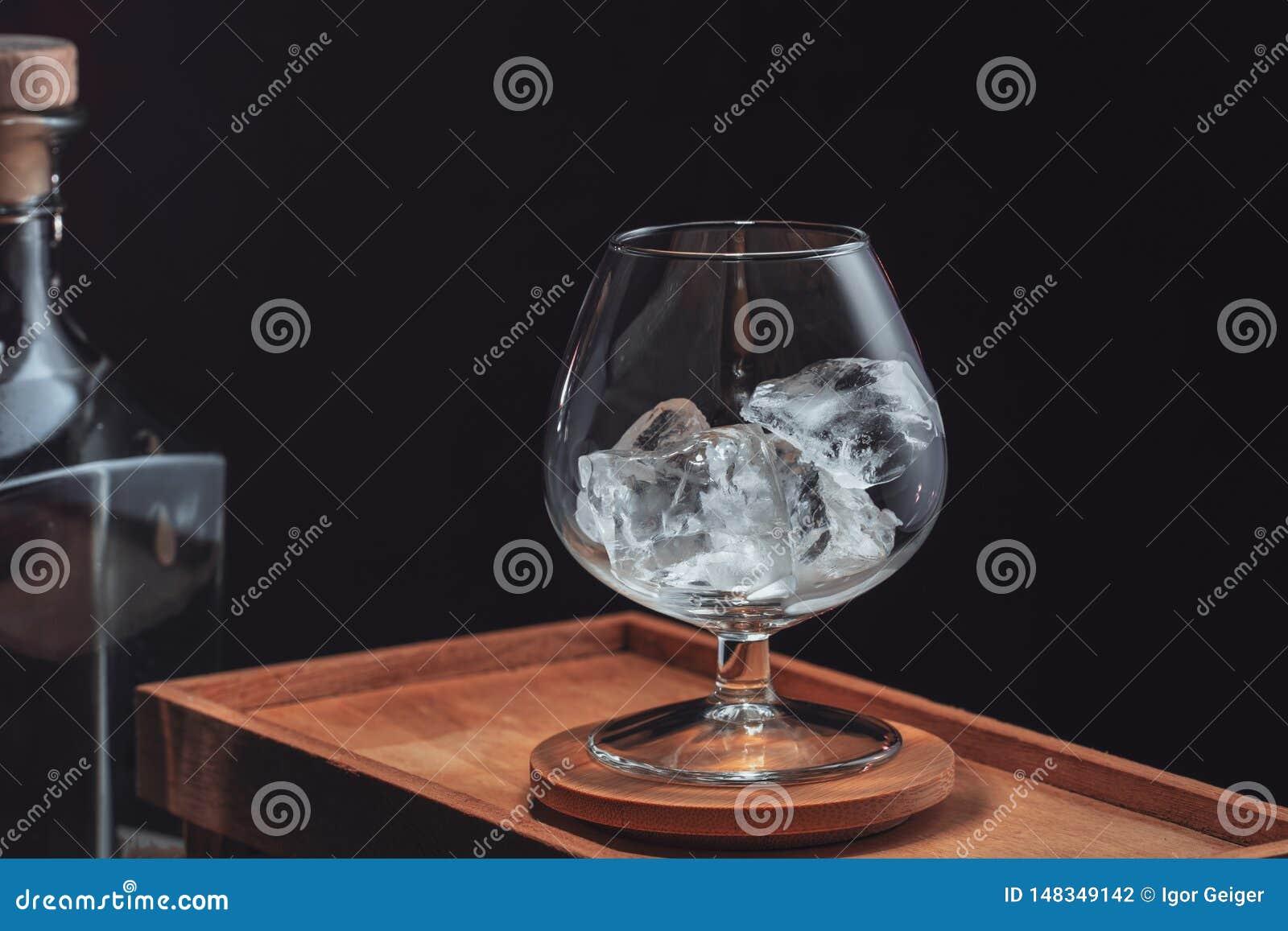 Gelo lascado em um vidro de aguardente transparente, em uma caixa de madeira em um fundo preto