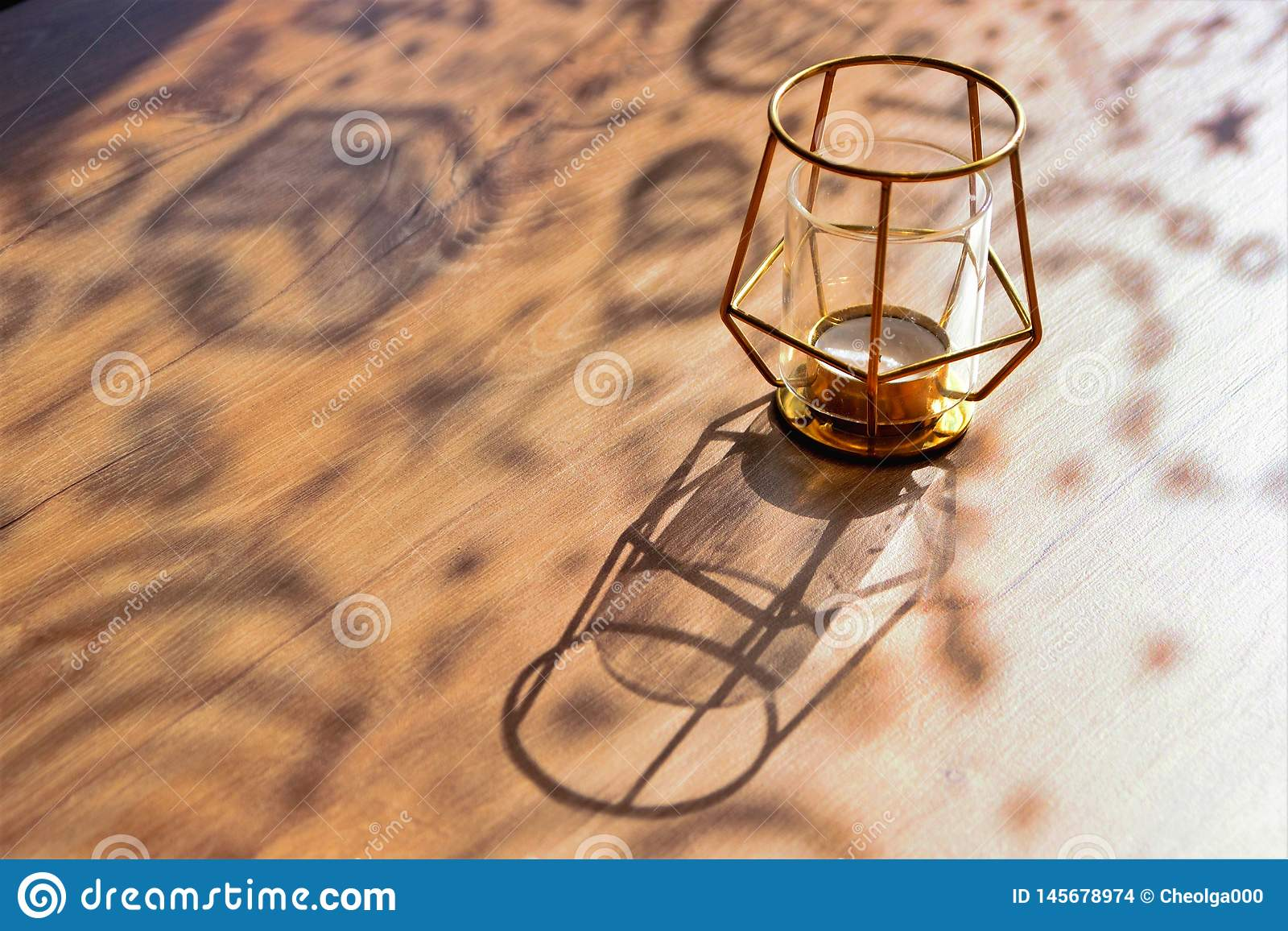 Gelockte Schatten auf einem Holztisch an einem sonnigen Tag, Designerkerzenständer, Nahaufnahme, selektiver Fokus, Kopienraum