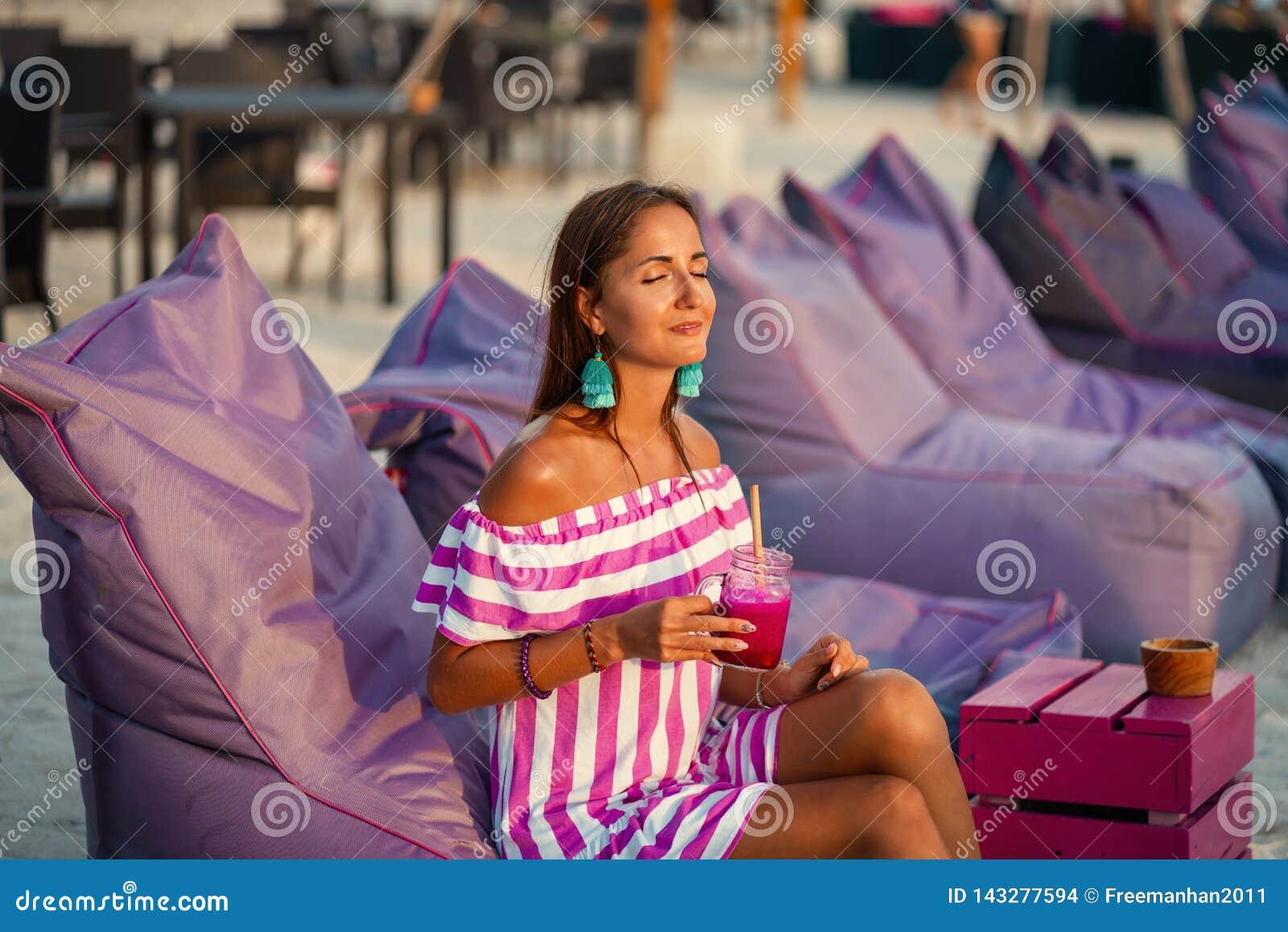 Gelooide mooie vrouw die op de strandbanken rusten en een cocktail drinken Het meisje glimlacht en geniet van de zon Het kuuroord
