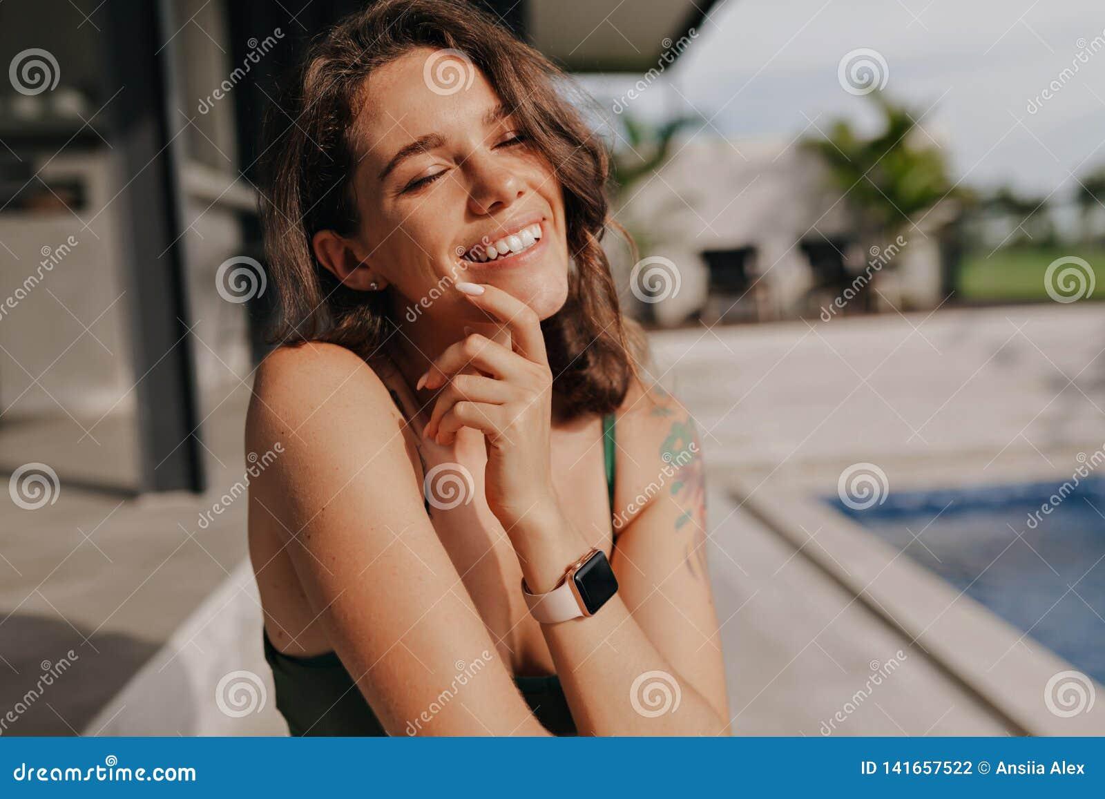 Gelukkig aanbiddelijk glimlachend meisje met gesloten ogen en romantische glimlachzitting in zonneschijn dichtbij de pool