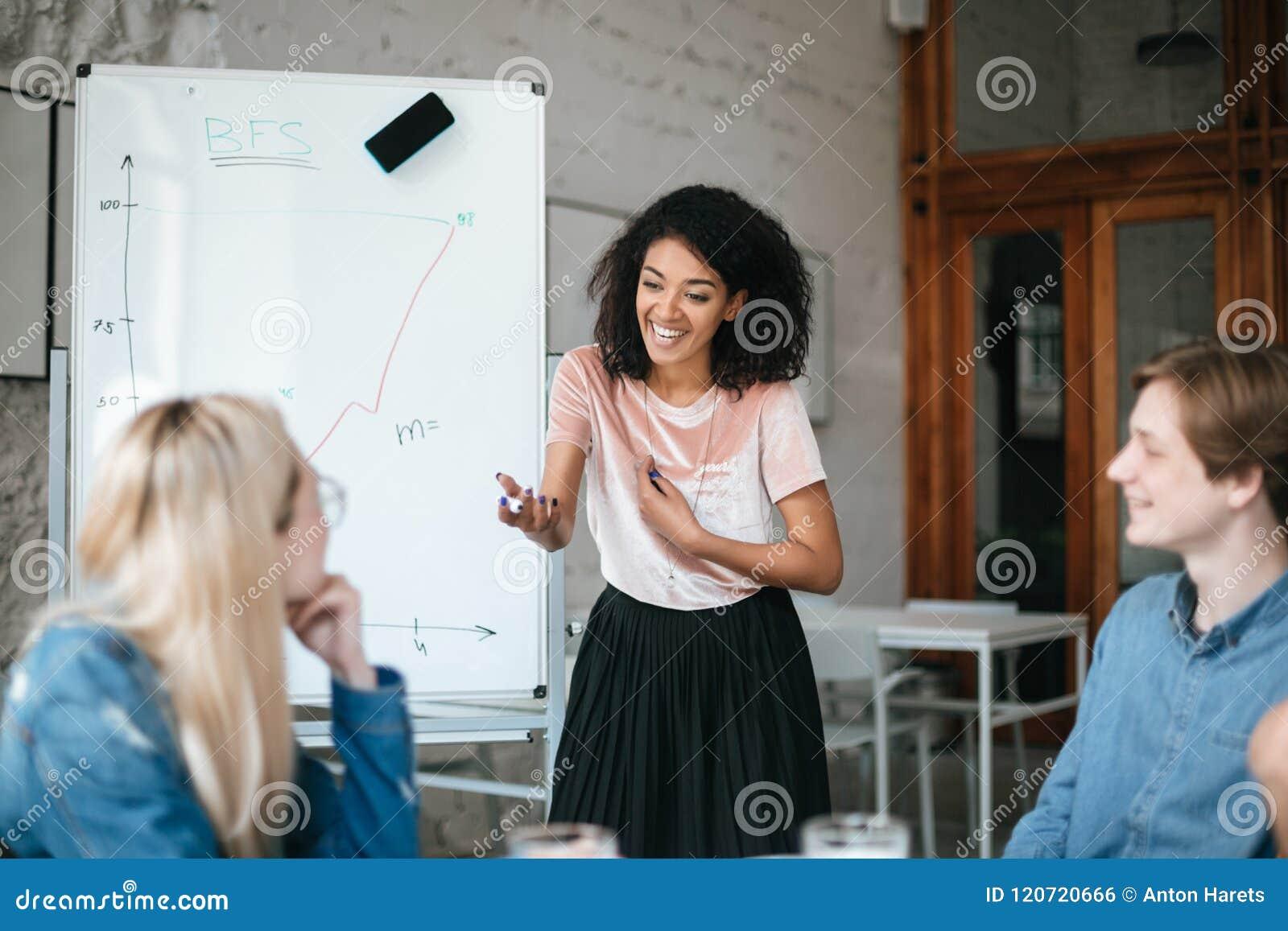 Gelukkig Afrikaans Amerikaans meisje die zich dichtbij raad bevinden en nieuw project bespreken met collega s in bureau Groep het