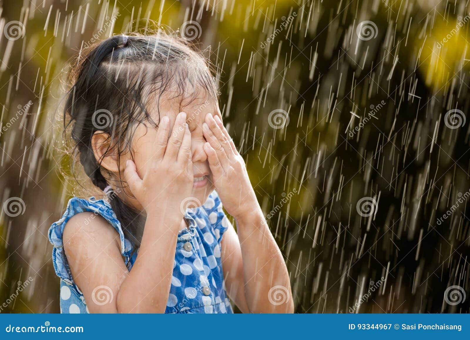Gelukkig Aziatisch meisje die pret met de regen hebben te spelen