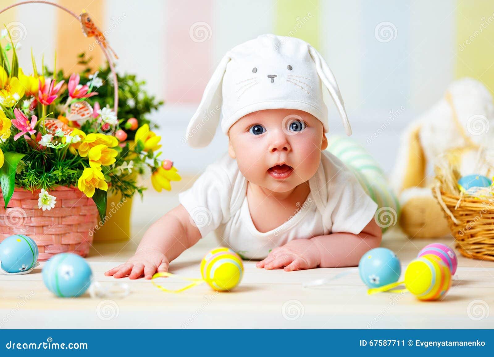 Gelukkig babykind met Paashaasoren en eieren en bloemen