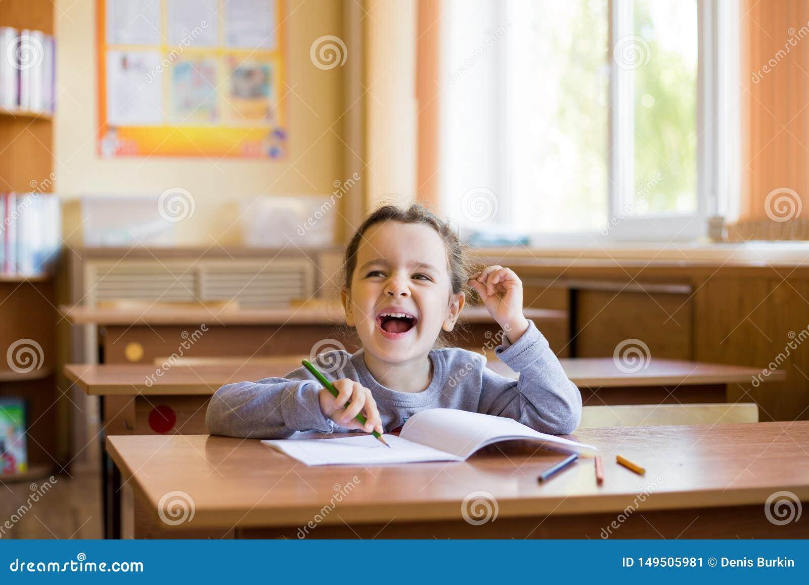 Gelukkig begint weinig het glimlachen meisjeszitting bij bureau in klassenruimte en zorgvuldig in een zuiver notitieboekje te tre