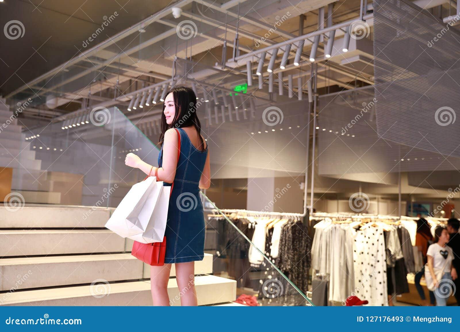 Gelukkig Chinees Oostelijk oosters jong in de vrouwenmeisje die van Azië in wandelgalerij met zakken het winkelen vensterachtergr