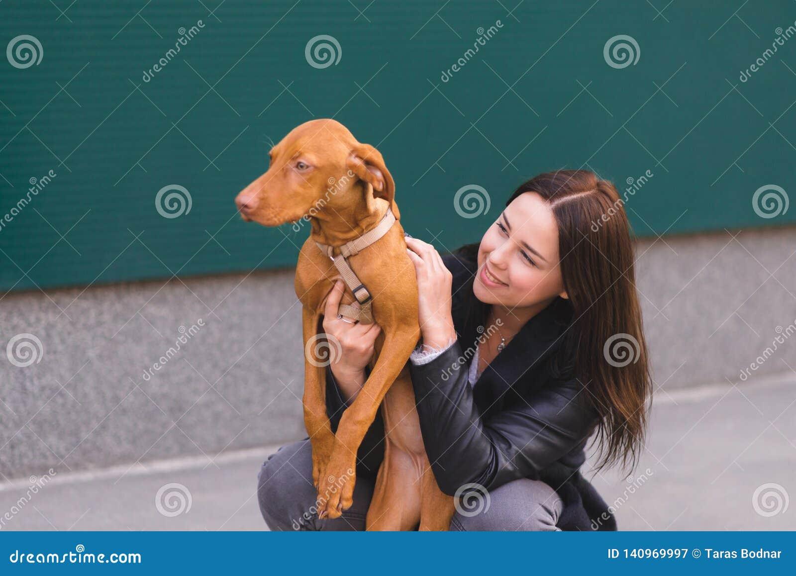 Gelukkig eigenaar en huisdier bij de achtergrond van de muur De handeling koestert een hond voor een gang Liefde aan dieren