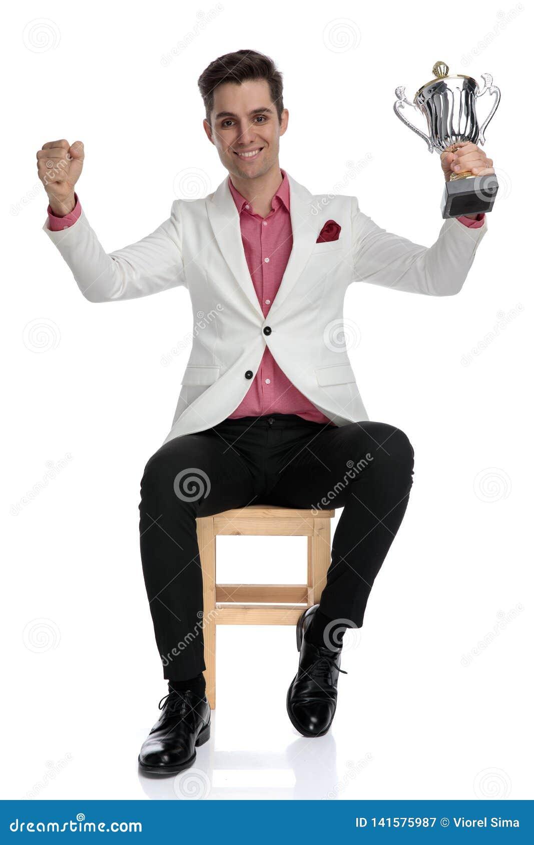 Gelukkig elegant zakenman het vieren succes door een trofee tegen te houden