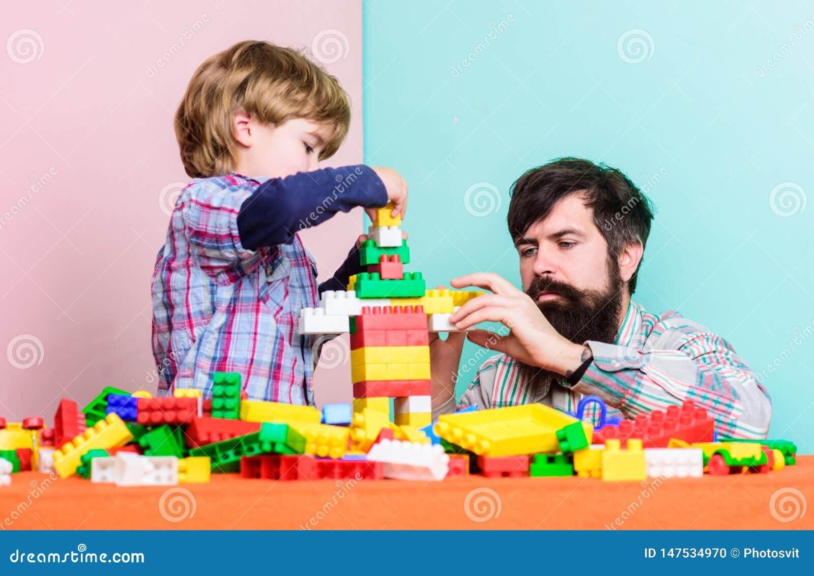 Gelukkig familieconcept de bouwhuis met kleurrijke aannemer Kindontwikkeling kleine jongen met papa die samen spelen
