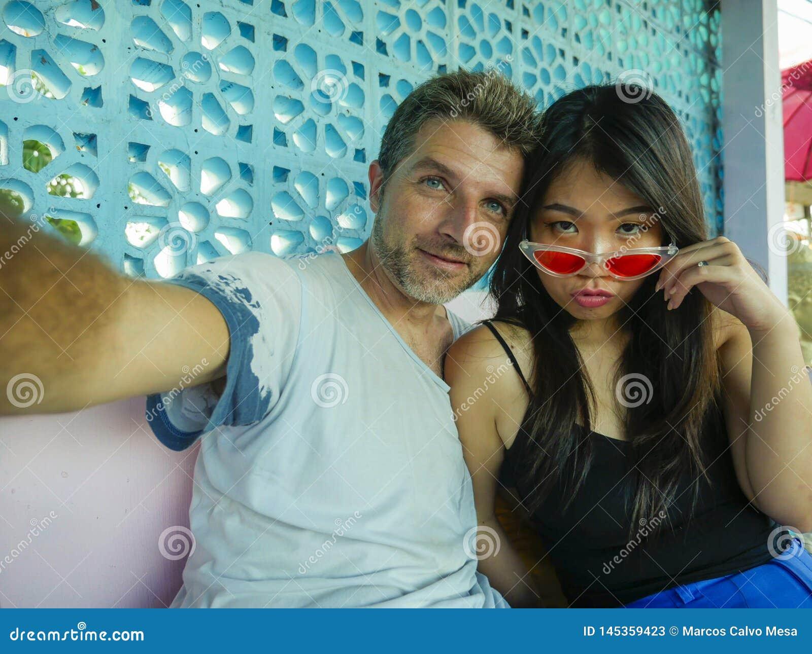 Gelukkig gemengd het behoren tot een bepaald raspaar in liefde glimlachen vrolijk met de knappe Kaukasische mens en mooie Aziatis