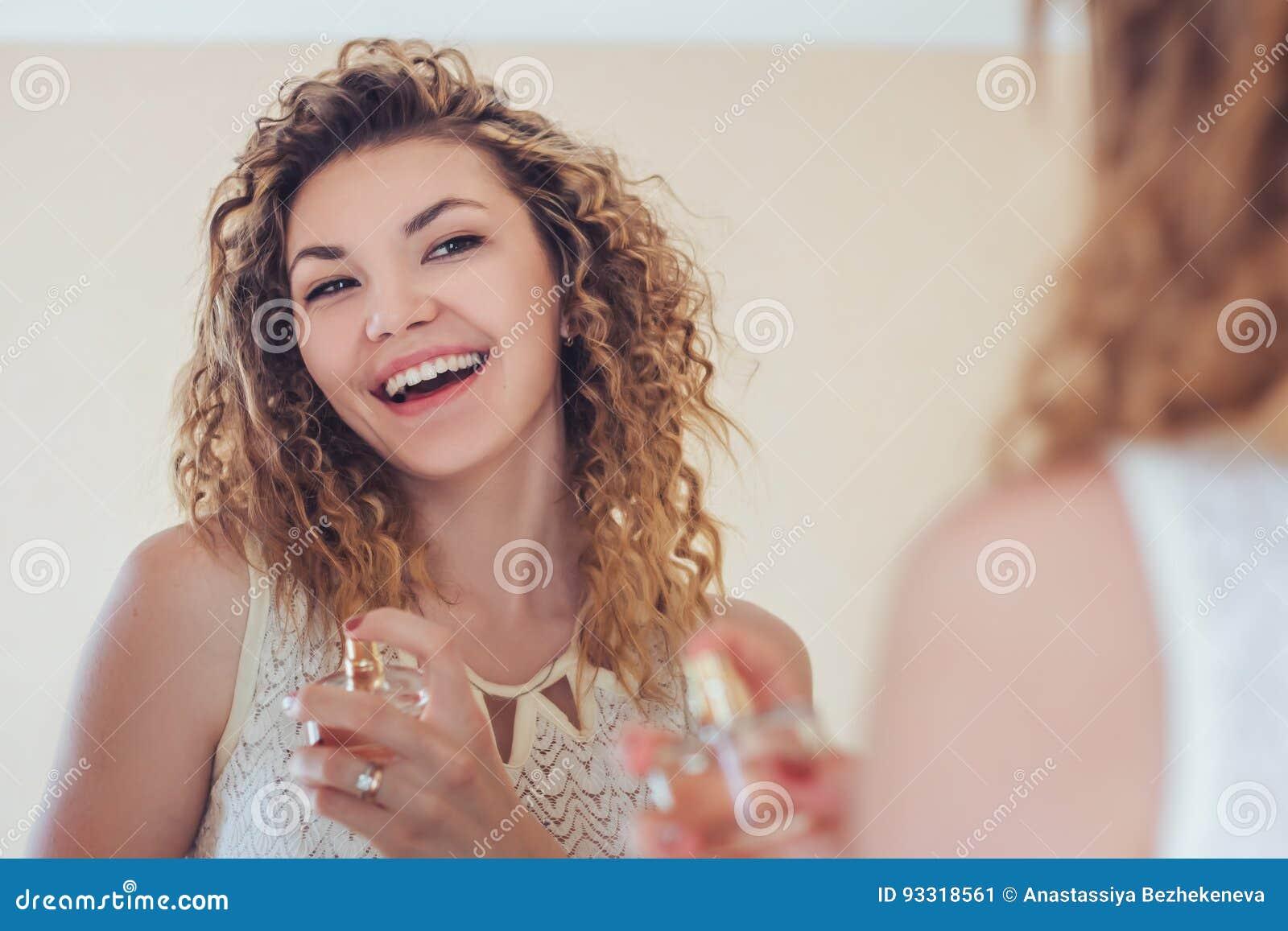 Gelukkig geparfumeerd meisje het bekijken spiegel