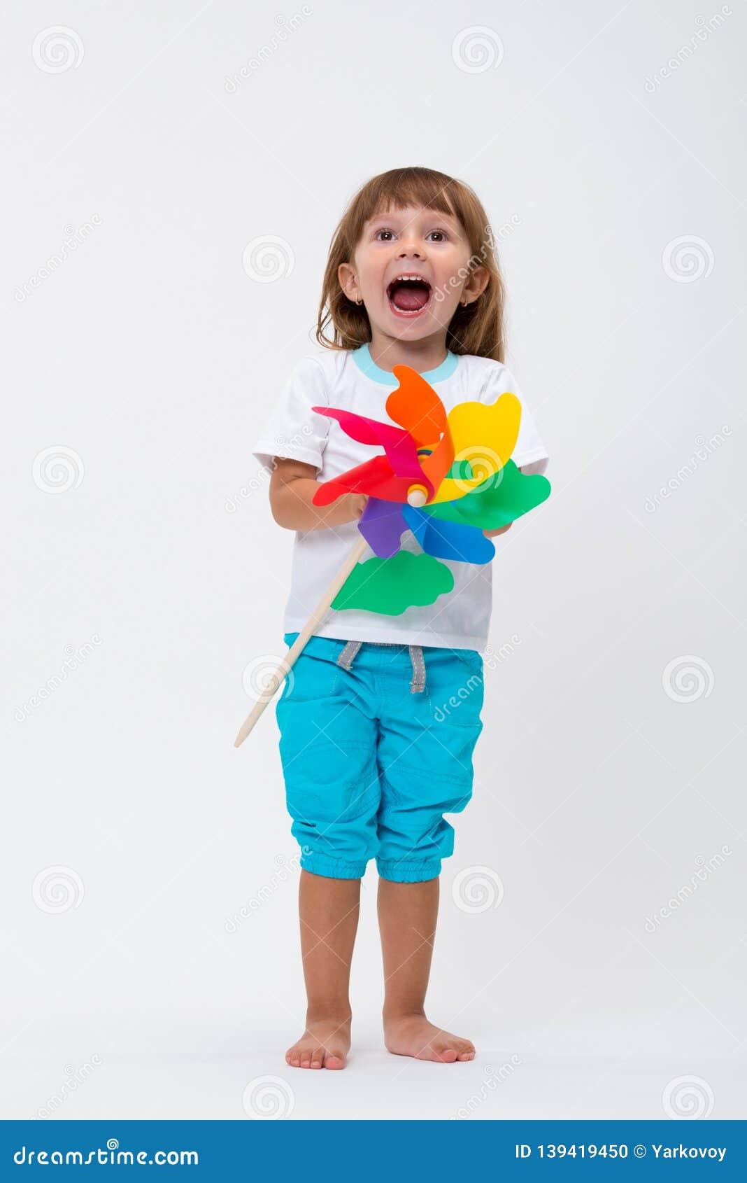 Gelukkig glimlachend meisje die een kleurrijke die stuk speelgoed vuurradwindmolen houden op witte achtergrond wordt geïsoleerd