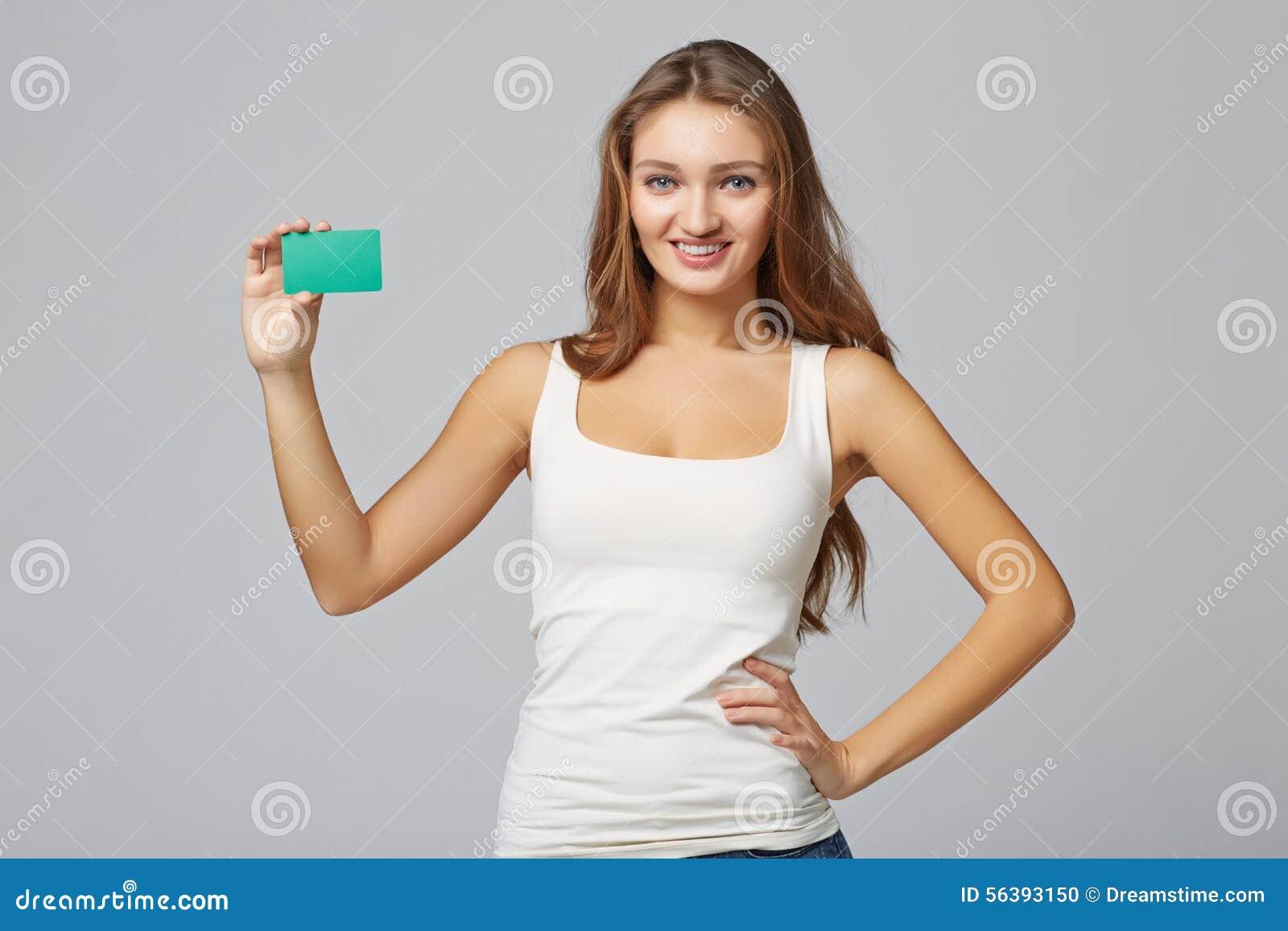 Gelukkig glimlachend meisje in toevallige kleding, die lege creditcard tonen