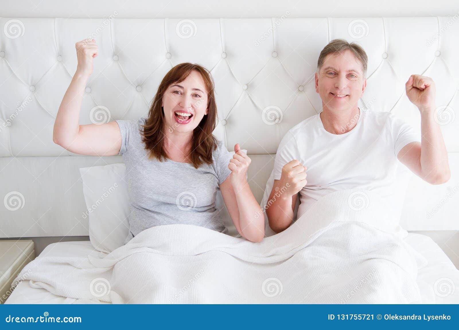 Gelukkig glimlachend middenleeftijdspaar in bed in t-shirt Gezonde familieverhoudingen De ruimte van het exemplaar