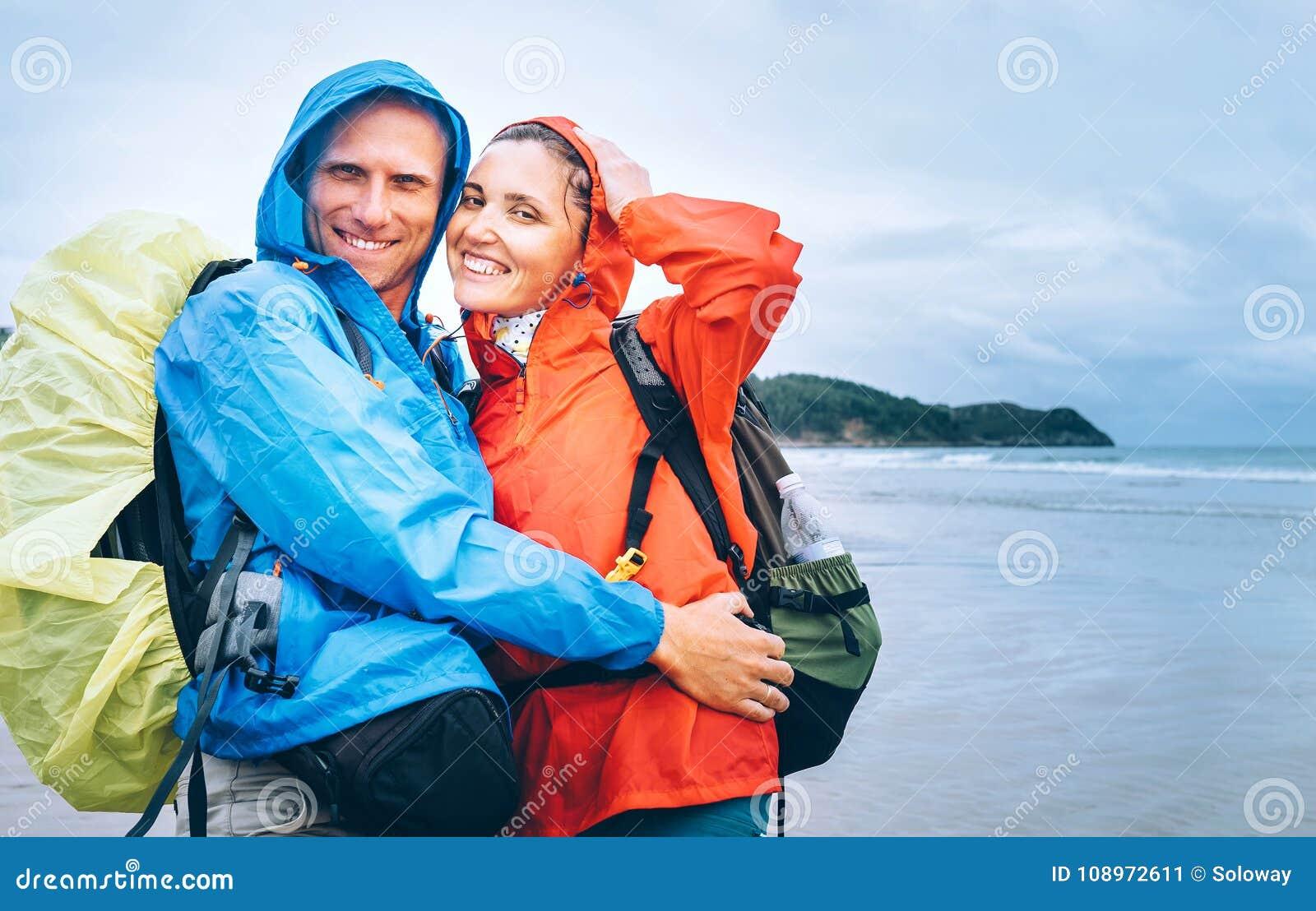 Gelukkig glimlachend reizigerspaar in regenachtige dag op het oceaanstrand