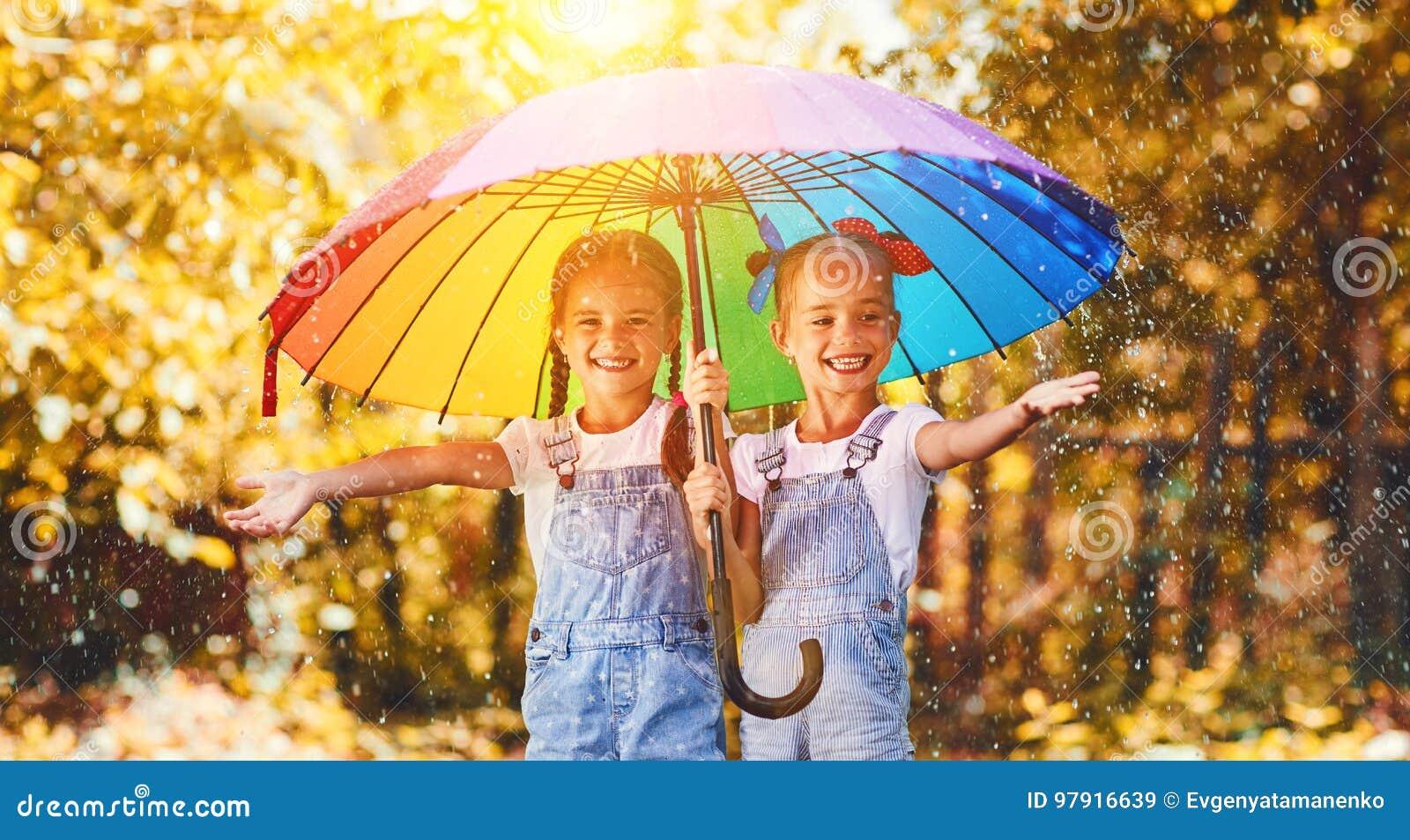 Gelukkig grappig het kindmeisje van zusterstweelingen met paraplu in de herfst