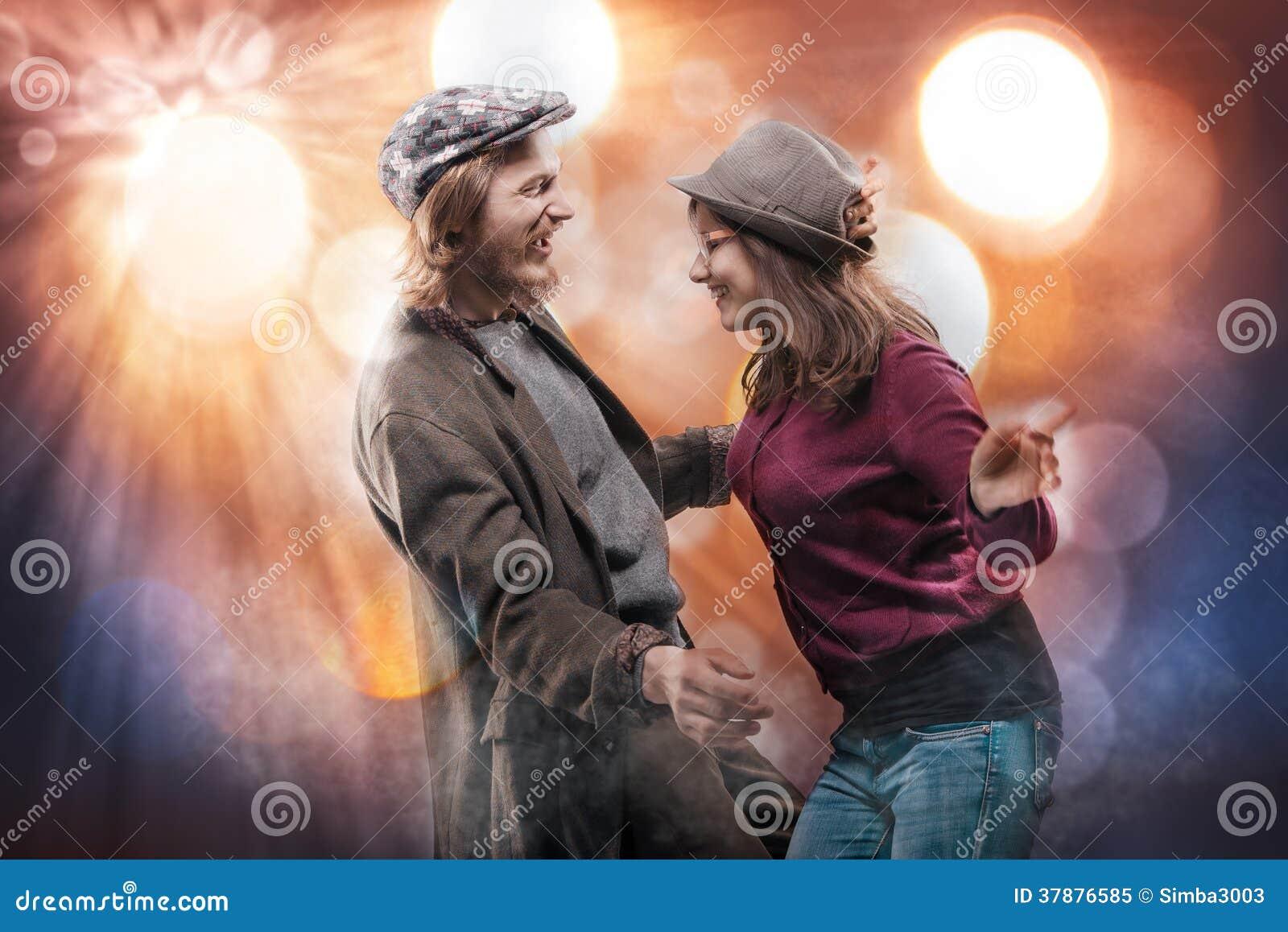 Gelukkig grappig jong paar die over abstracte achtergrond dansen