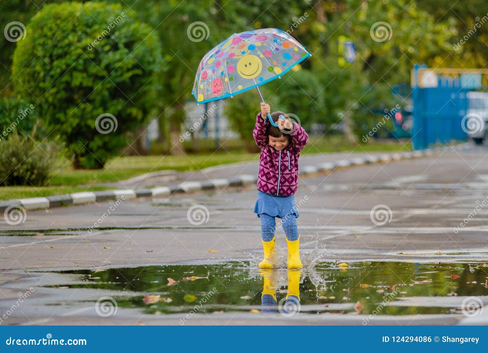 Gelukkig grappig kind met multicolored paraplu het springen vulklei in rubberlaarzen en het lachen