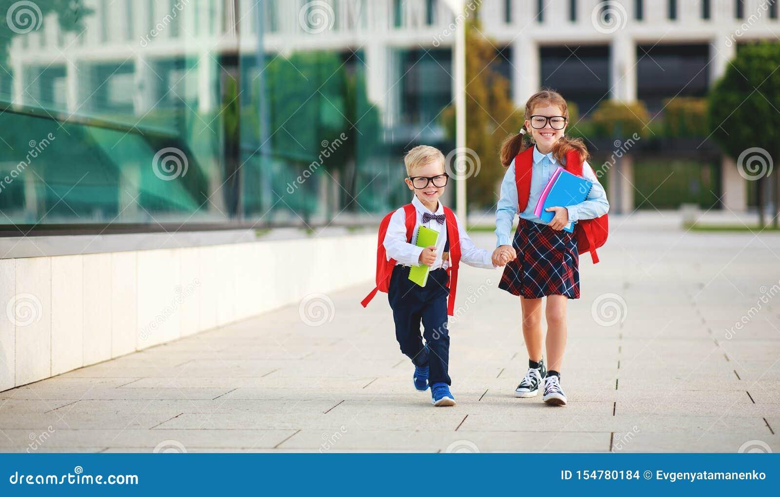 Gelukkig grappig kinderenschoolmeisje en de basisschool van de schooljongenstudent