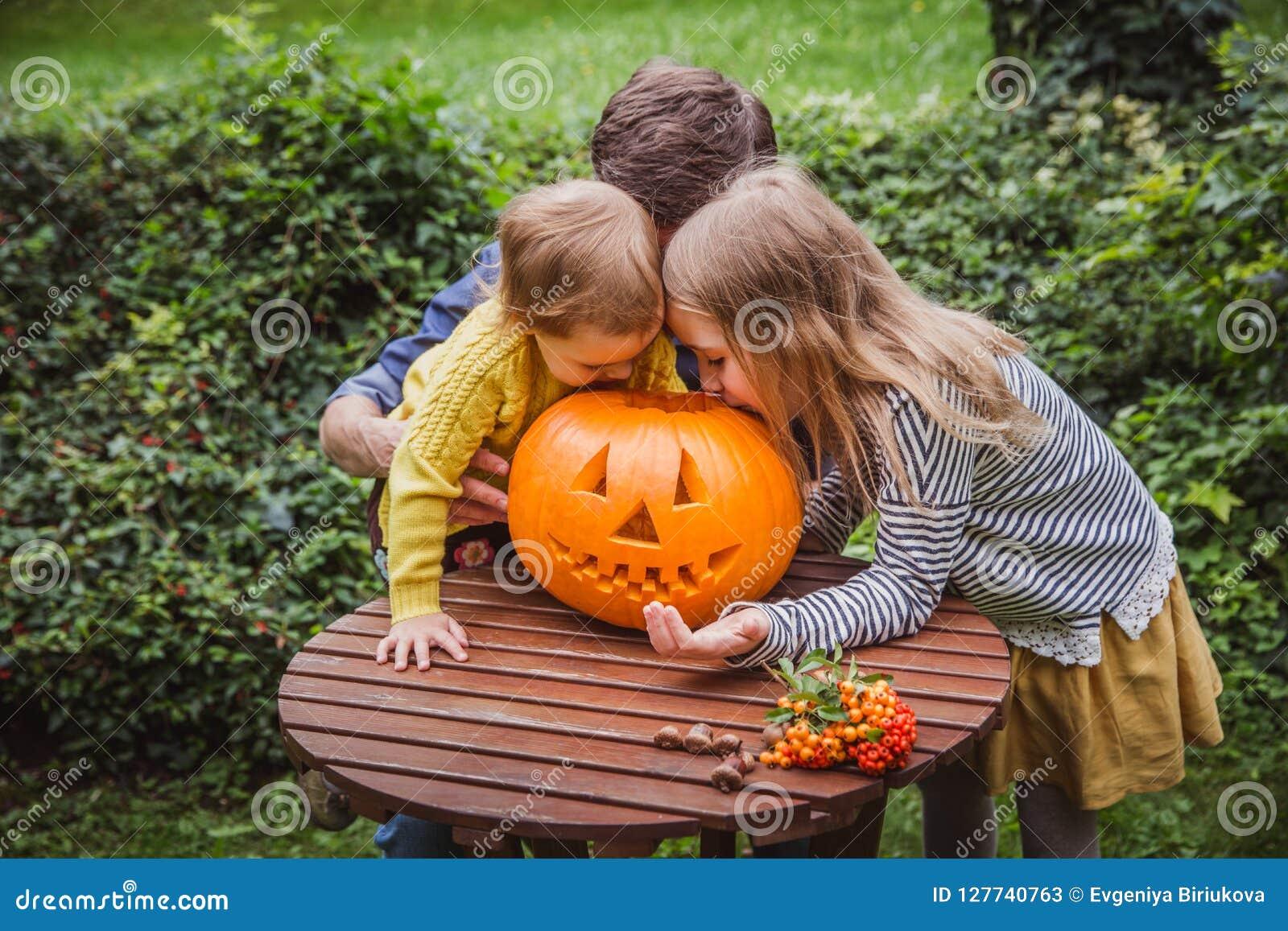 Gelukkig Halloween De vader en twee dochters kijken buiten binnen de gesneden pompoen voor Halloween