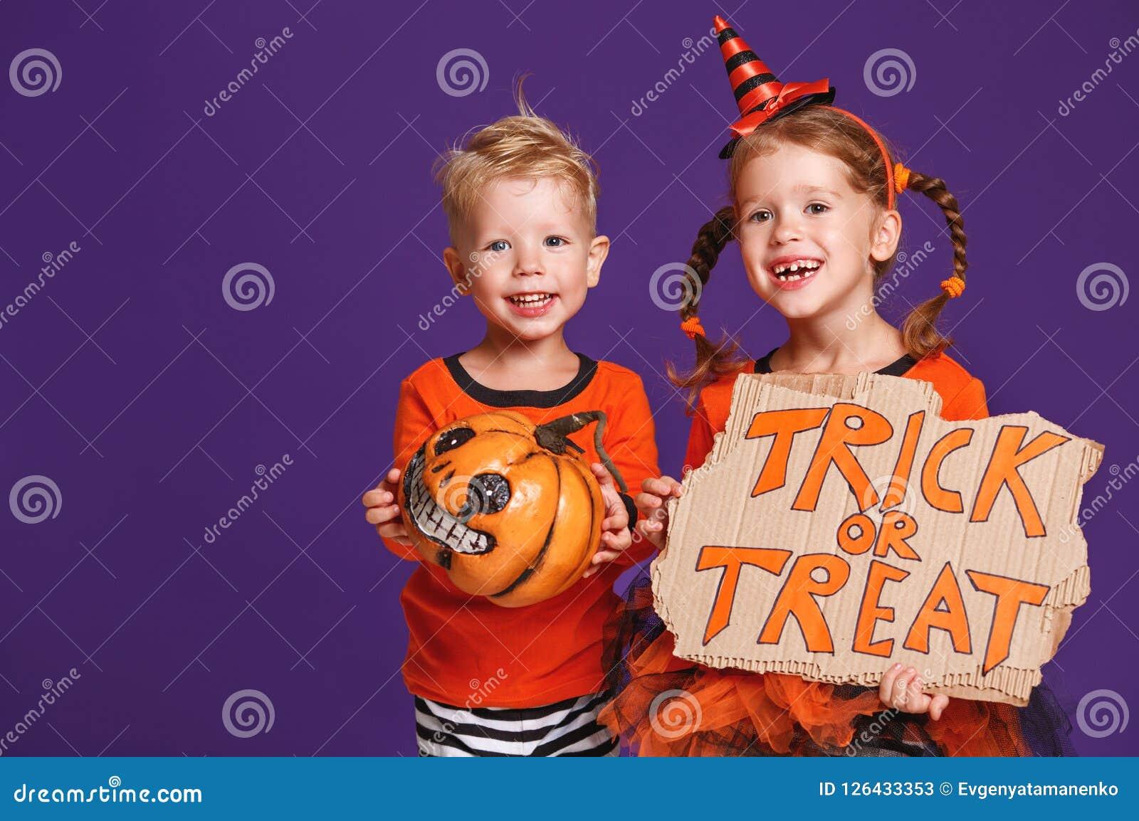 Gelukkig Halloween! vrolijke kinderen in kostuum met pompoenen op v