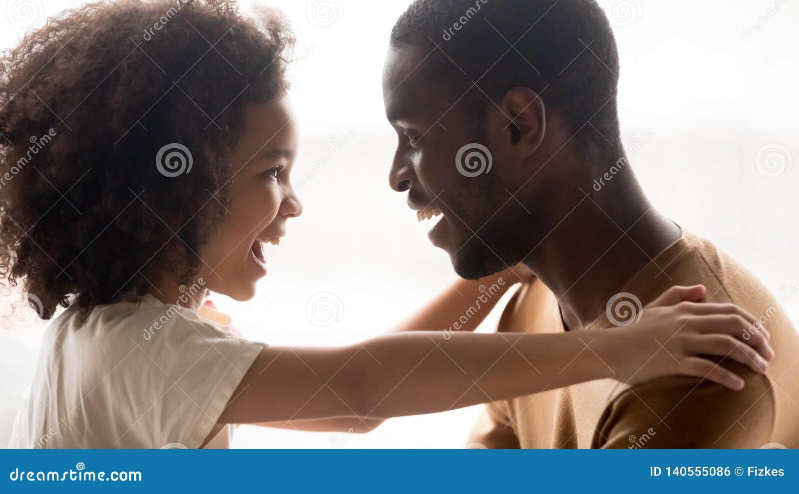 Gelukkig het kindmeisje die van het familie leuk mengen-ras het zwarte vader lachen omhelzen