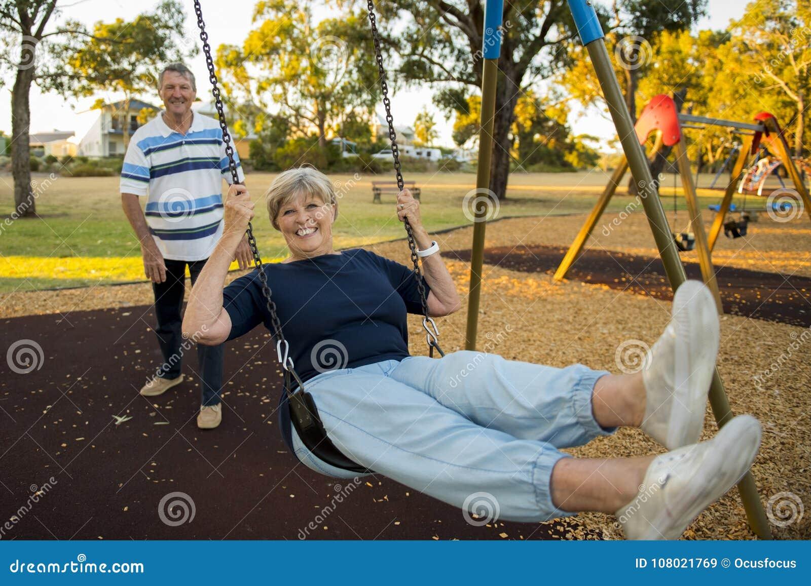 Gelukkig hoger Amerikaans paar rond 70 jaar het oude genieten van bij schommelingspark met vrouwen duwende echtgenoot die en pret