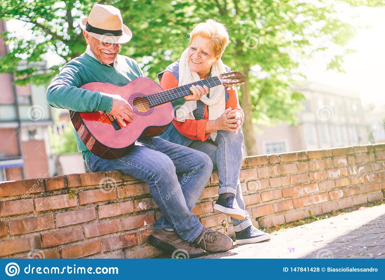 Gelukkig hoger paar die een gitaar spelen terwijl het zitten buiten op een muur op een zonnige dag