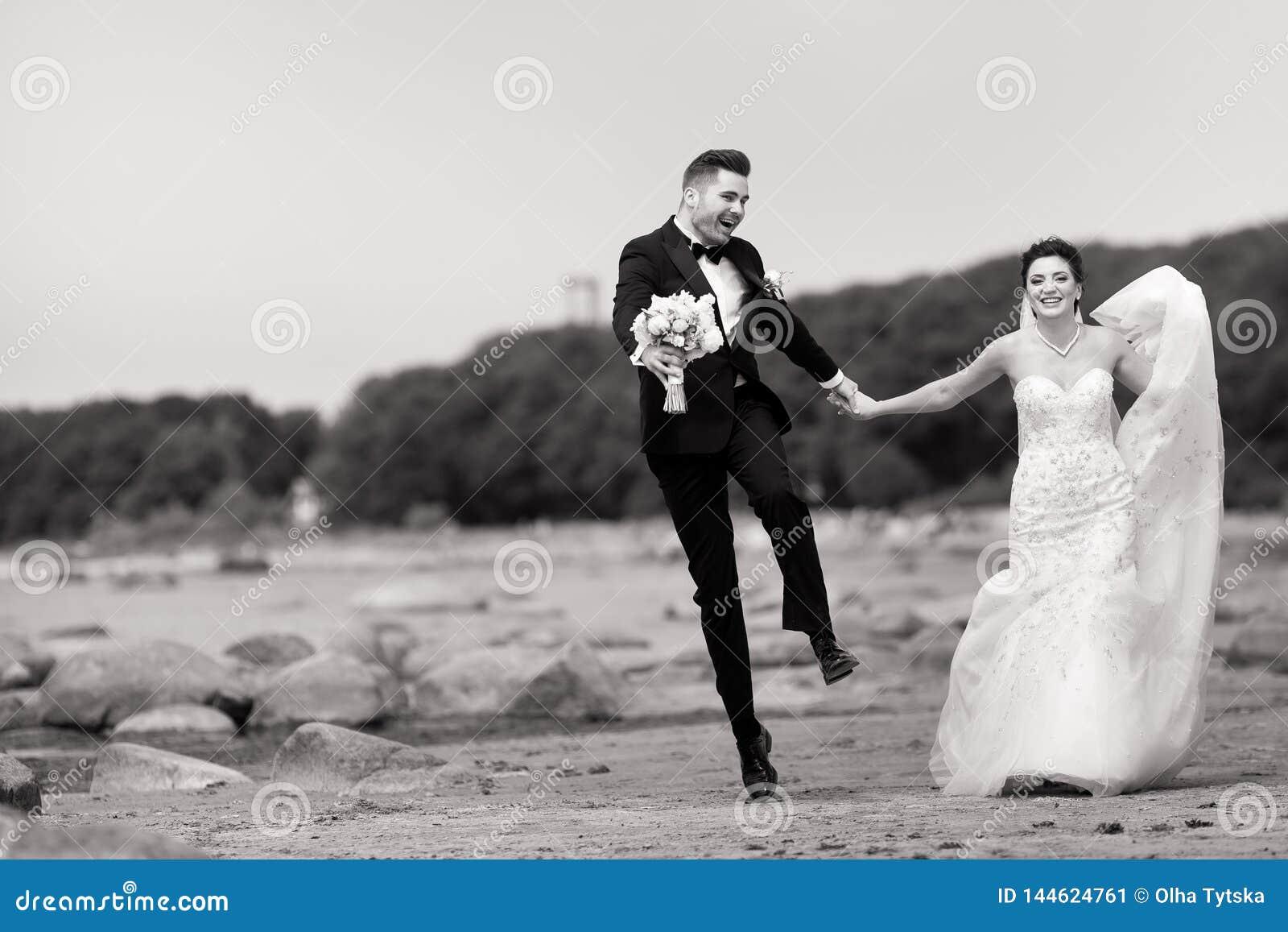 Gelukkig jong huwelijkspaar die pret op het strand hebben Rebecca 36