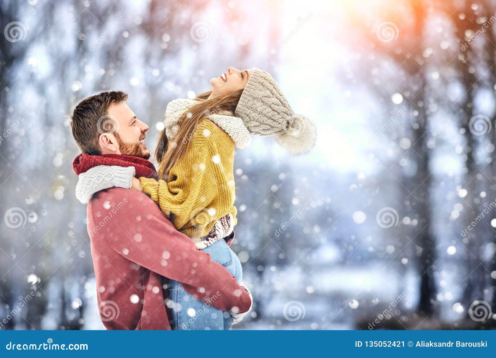 Gelukkig Jong Paar in de Winterpark die en pret hebben lachen Familie in openlucht